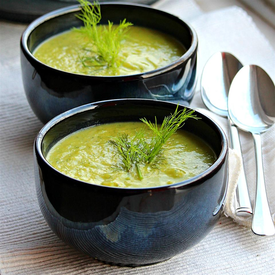portrait of two large bowls full of zucchini soup