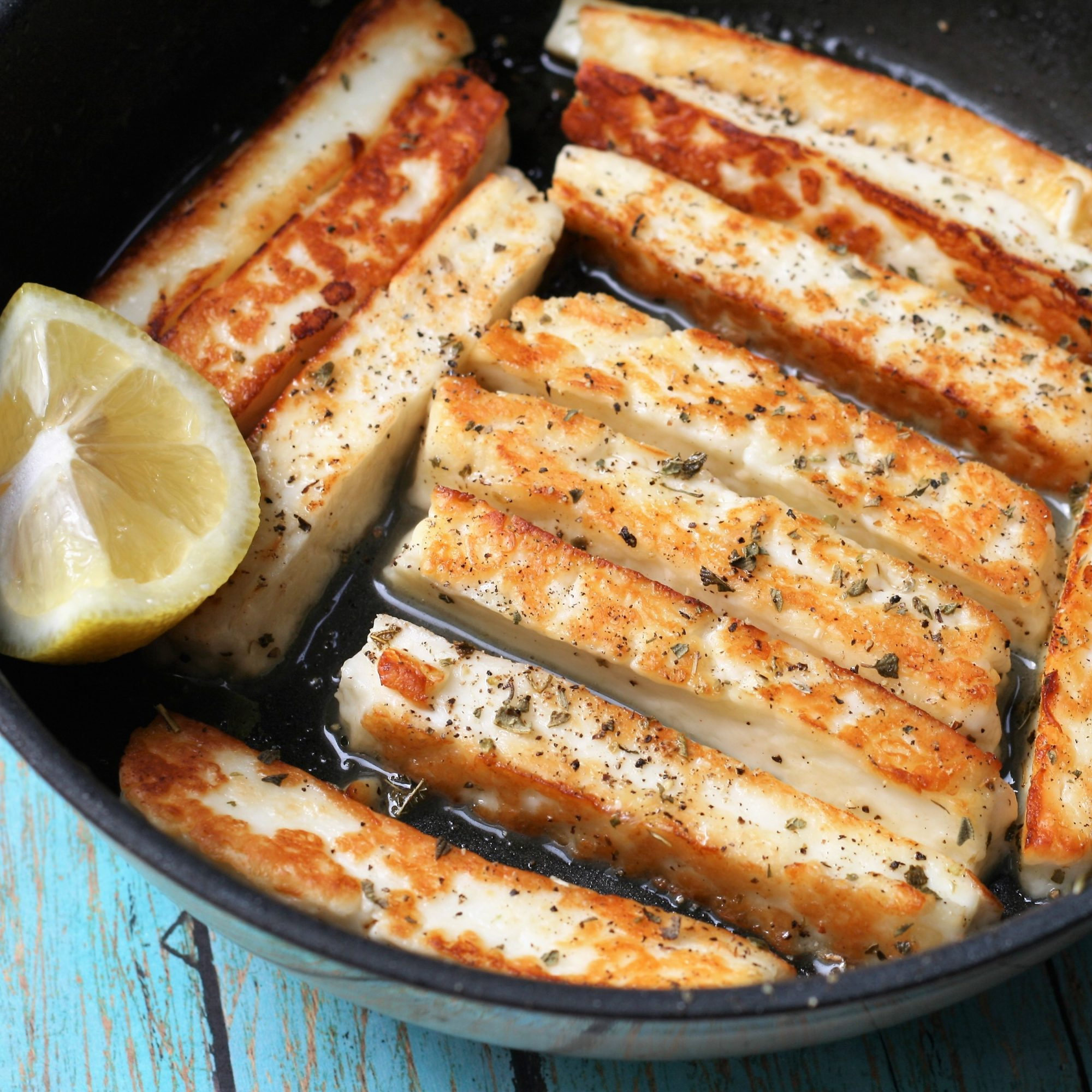 halloumi cheese fingers in a frying pan with lemon wedge