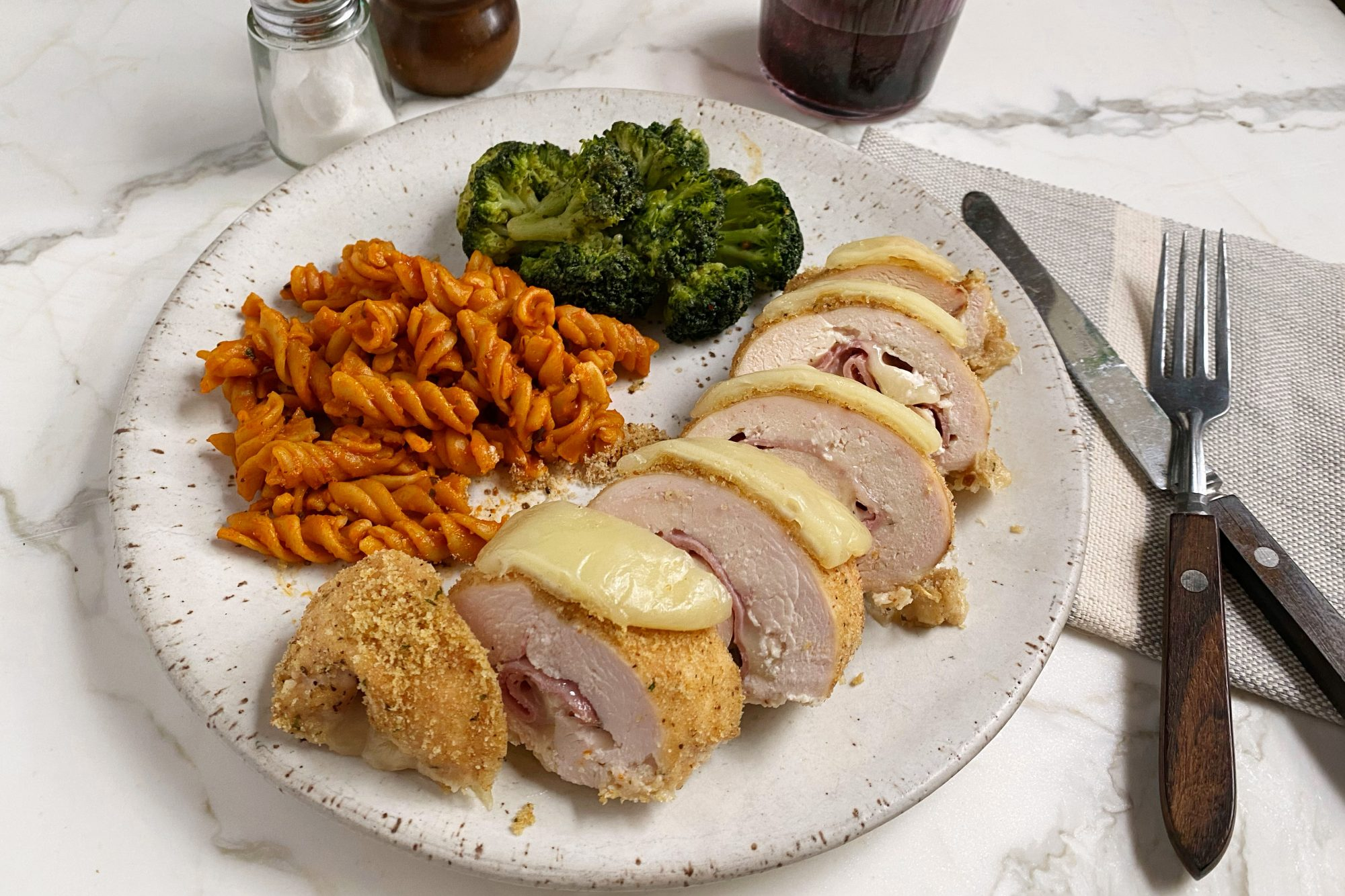 Sliced Chicken Cordon Blue on a dinner plate served with pasta and broccoli