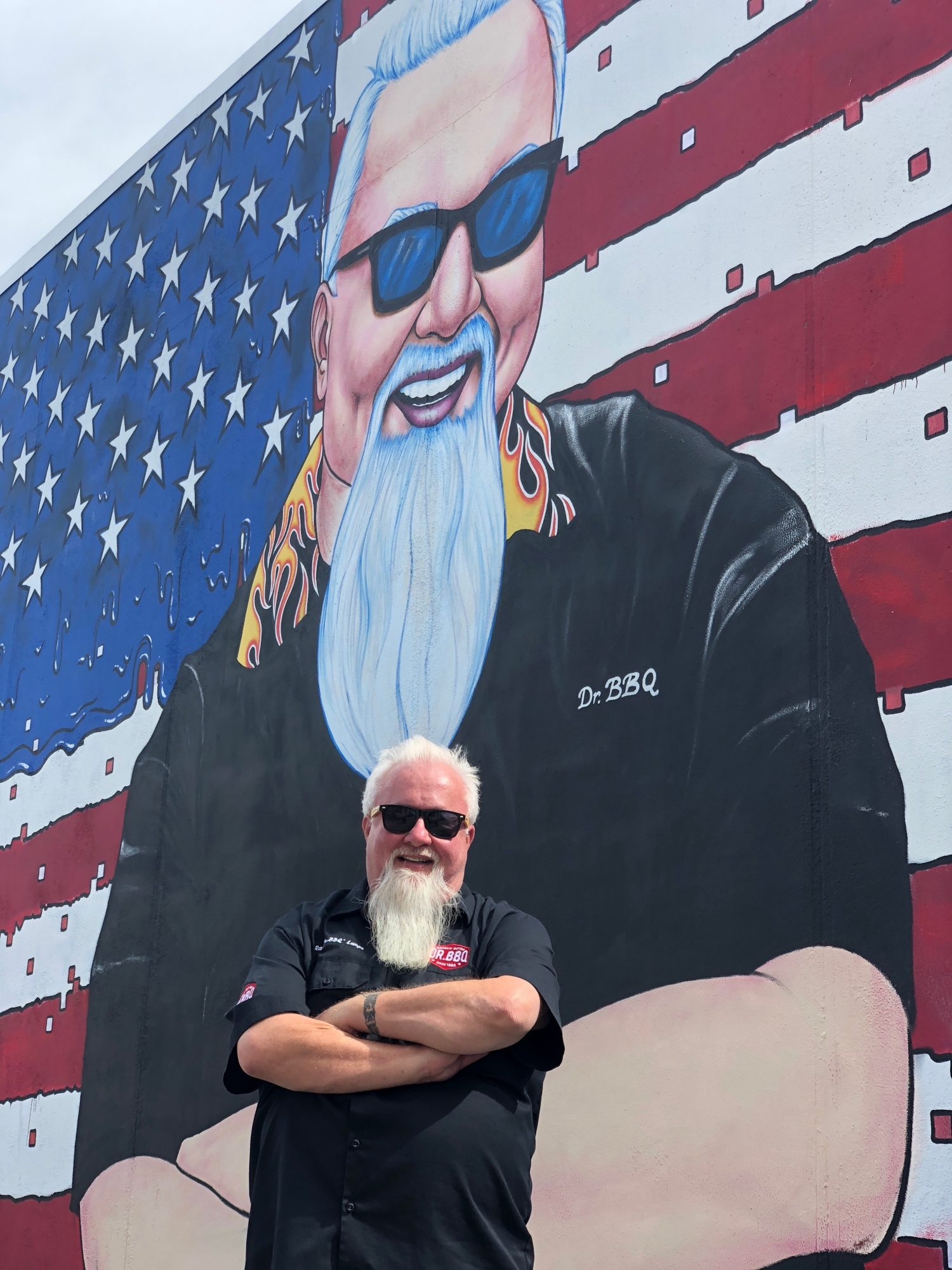 Ray Lampe standing in front of Dr. BBQ Mural