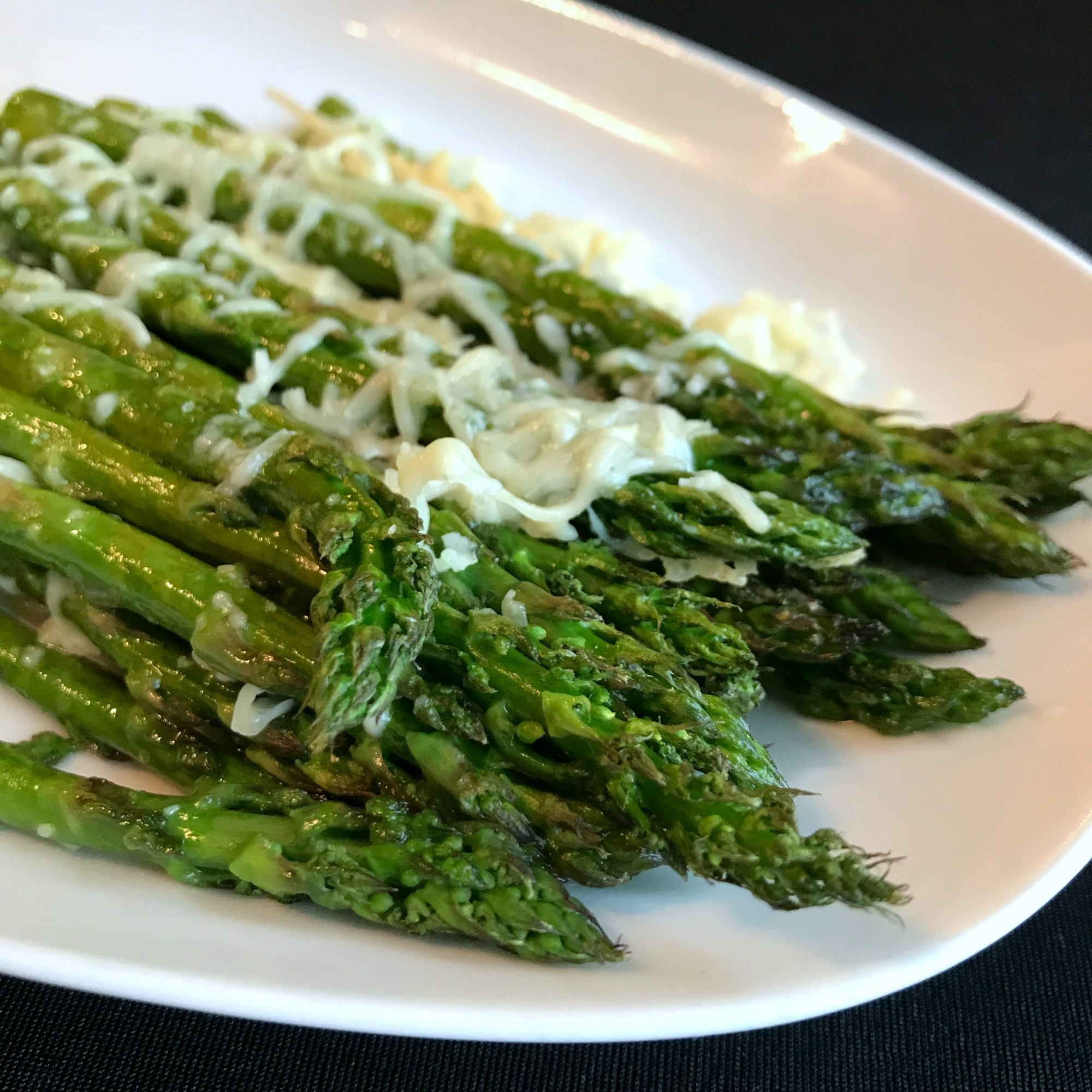 close up of roasted asparagus topped with Parmesan cheese