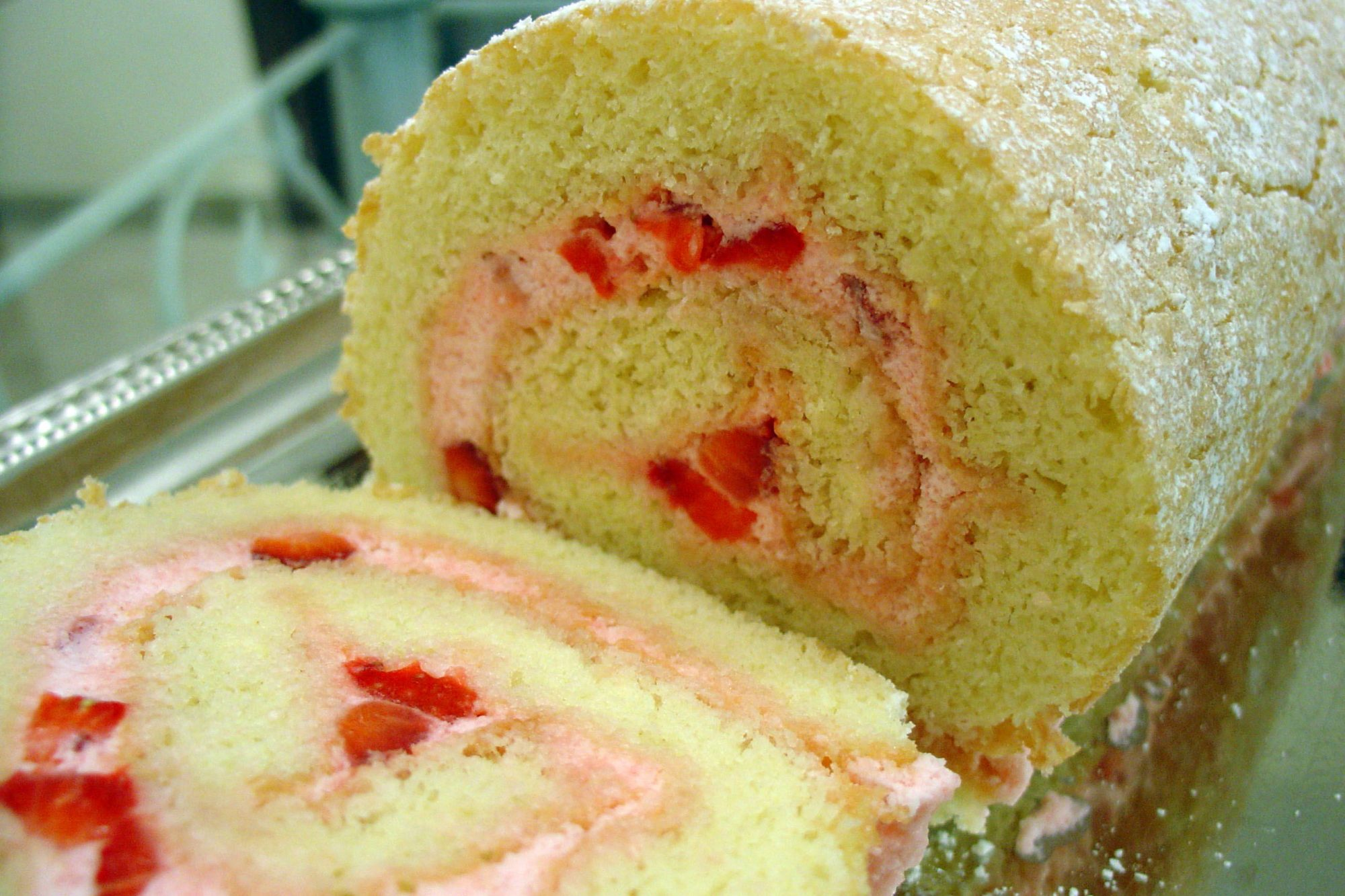 closeup of a Swiss roll cake sliced to show the swirl of strawberry cream filling