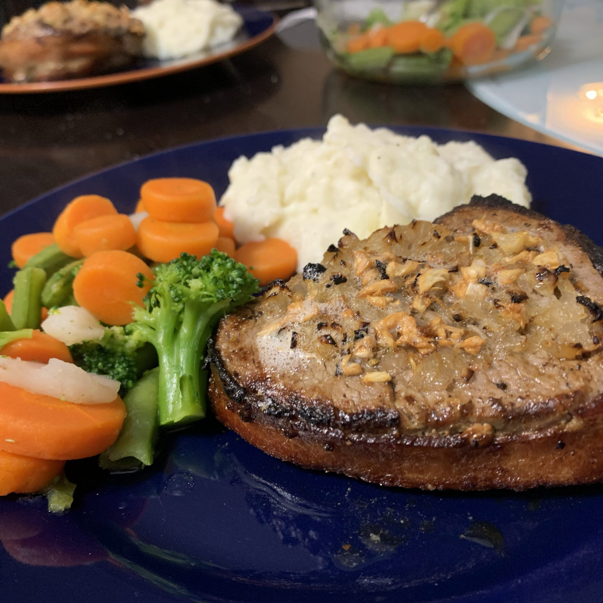 bacon wrapped filet served with mashed potatoes and veggies