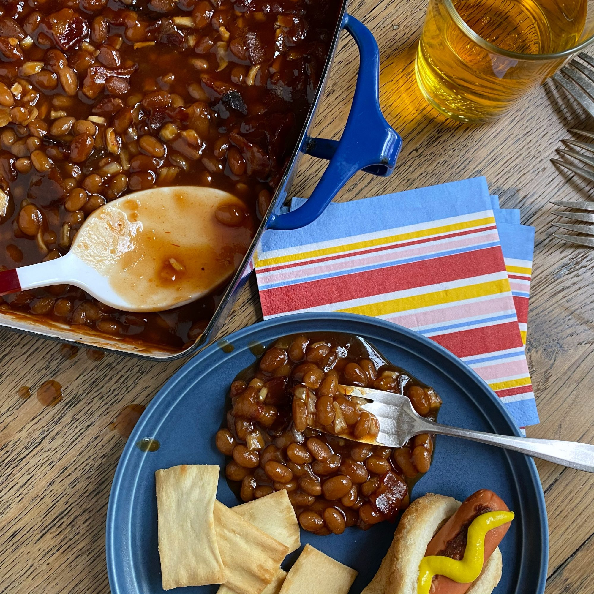 Casserole dish of down home baked beans. A small plate with a serving of beans and a hot dog sit near the casserole dish