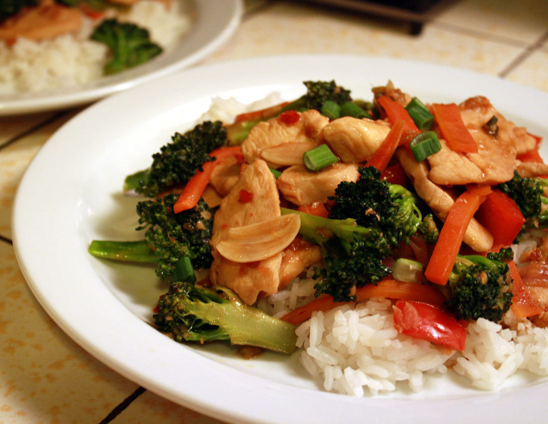 a plate of stir-fried chicken and vegetables served over rice