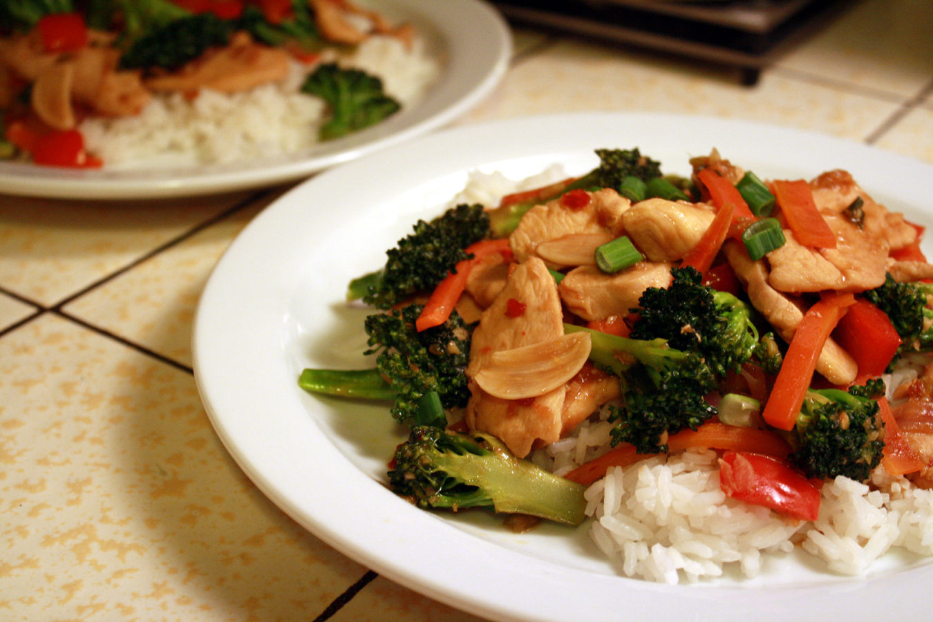 a plate of stir-fried chicken and vegetables on rice