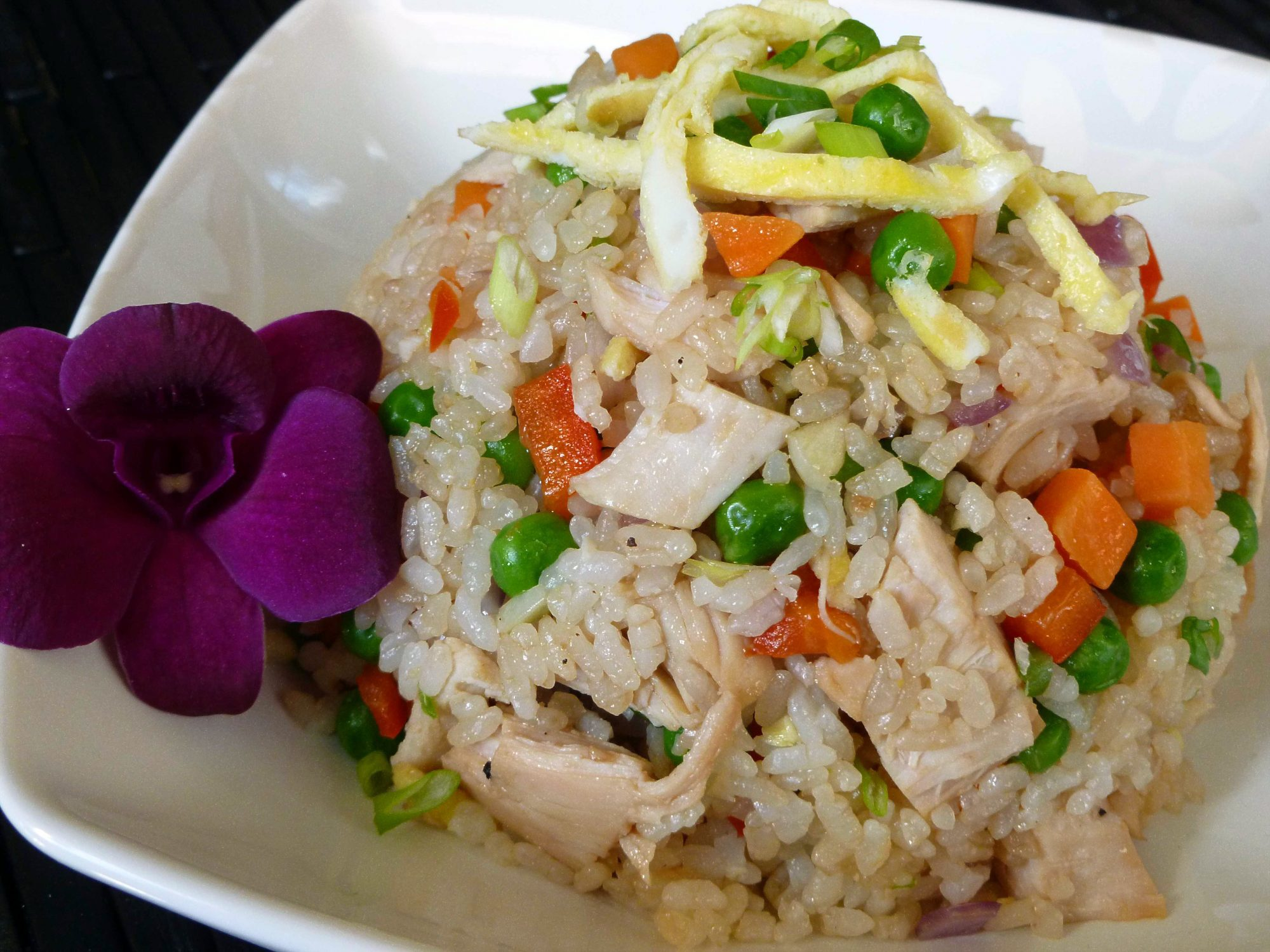a scoop of fried rice with chicken, diced carrot, and peas in a bowl garnished with strips of cooked egg