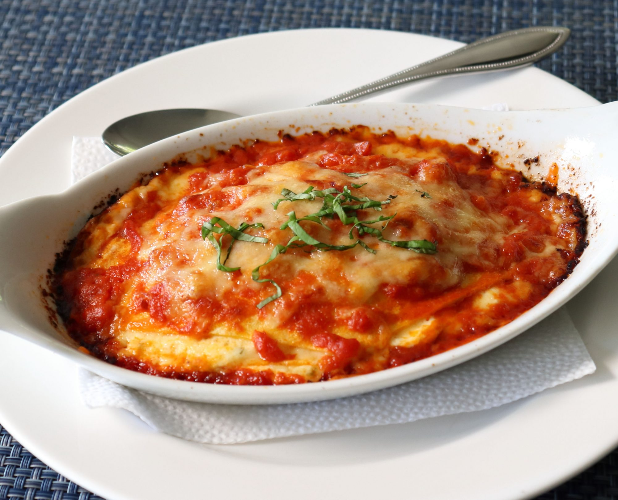top-down view of an oval ramekin on lasagna on a white plate
