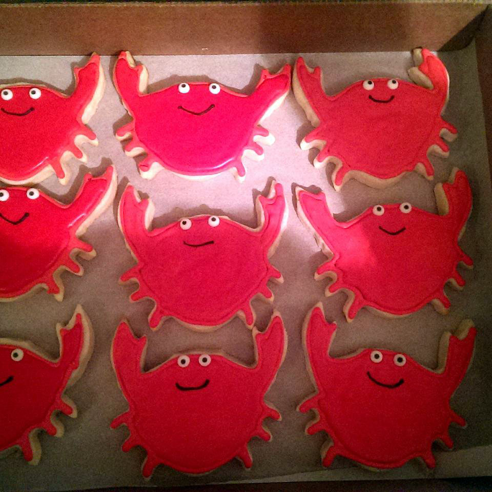 a box of crab-shaped cookies decorated with red icing and smiling faces