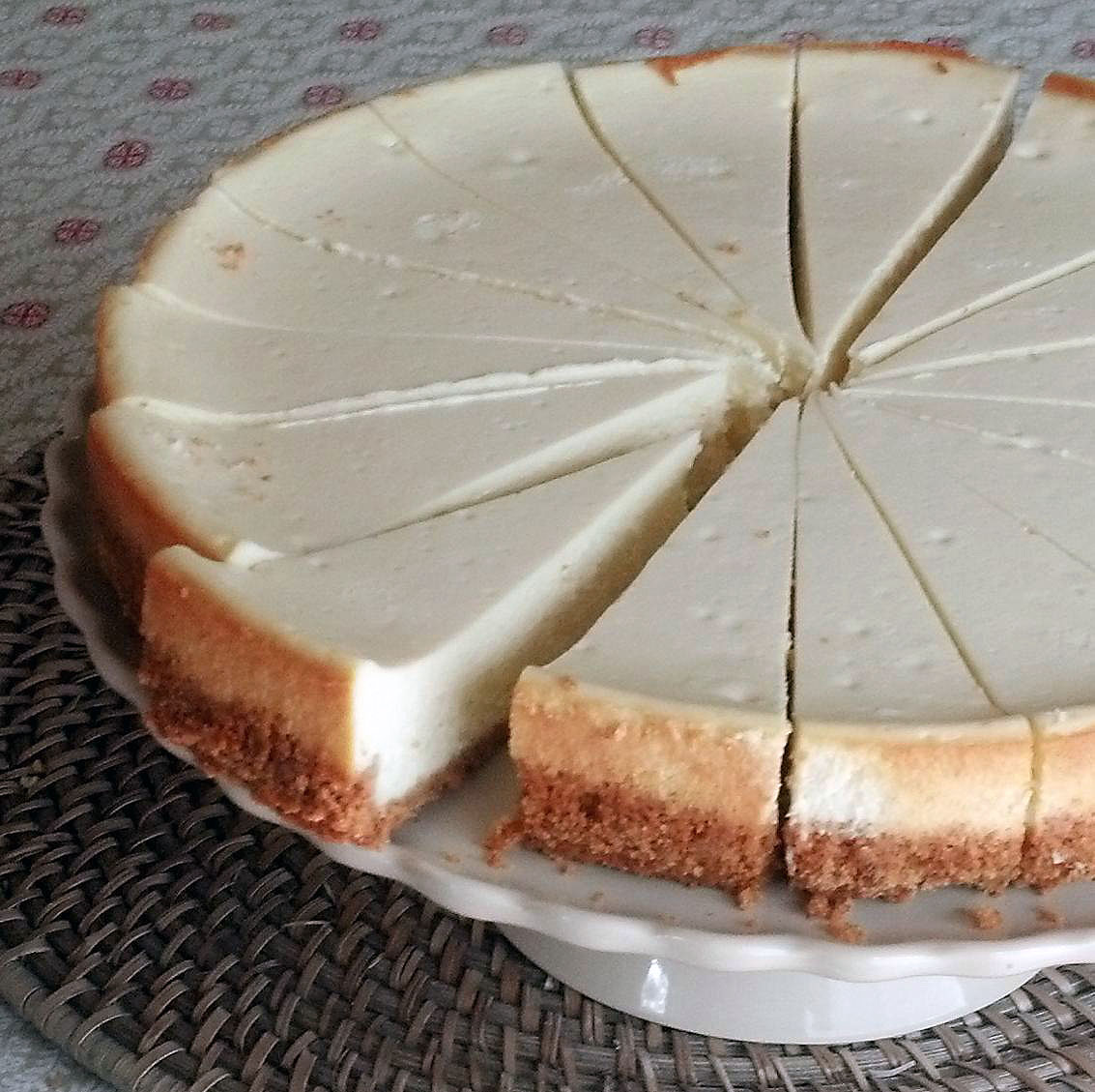 a plain cheesecake on a cake stand, cut into slices with one slice set apart ready to serve
