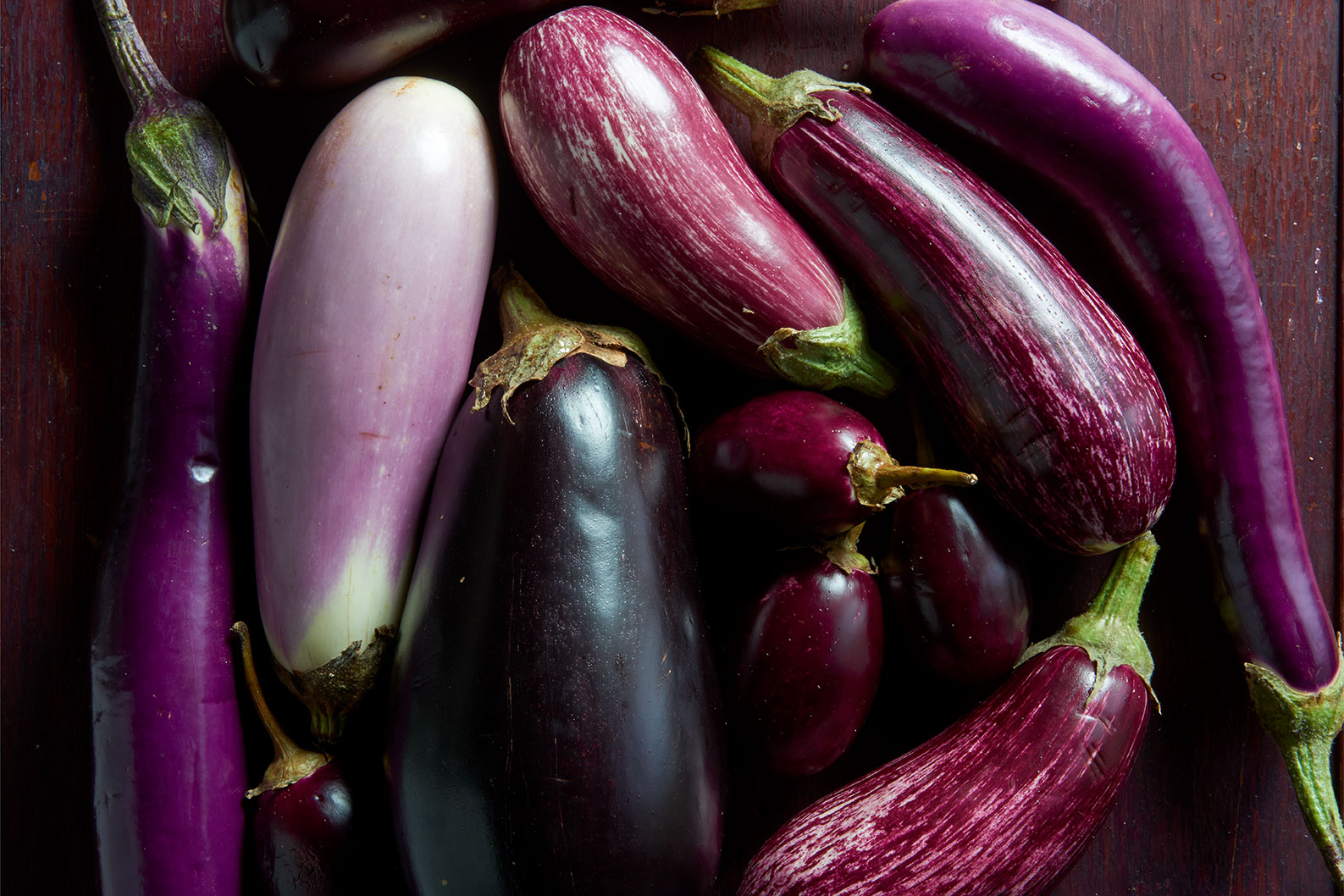 different types of eggplants on wooden table