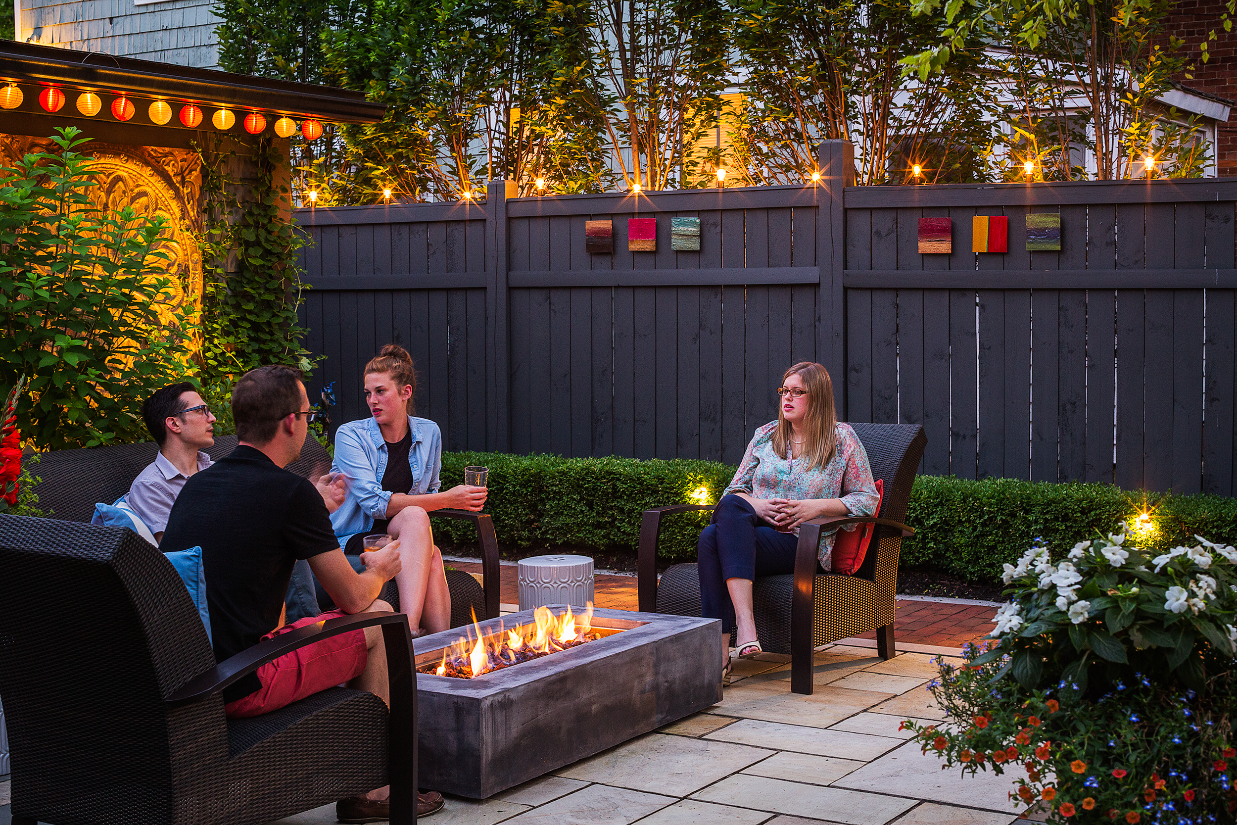 Accent lighting along fence, garage and landscaped areas; Friends sitting by burning fire pit at patio against illuminated fence