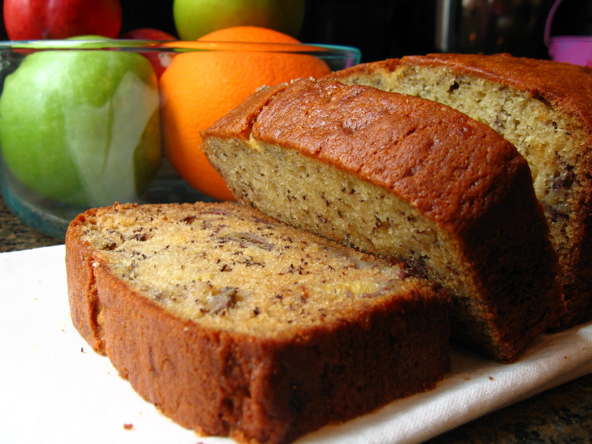 closeup of thickly sliced banana bread on a white platter with a fruit bowl in the background