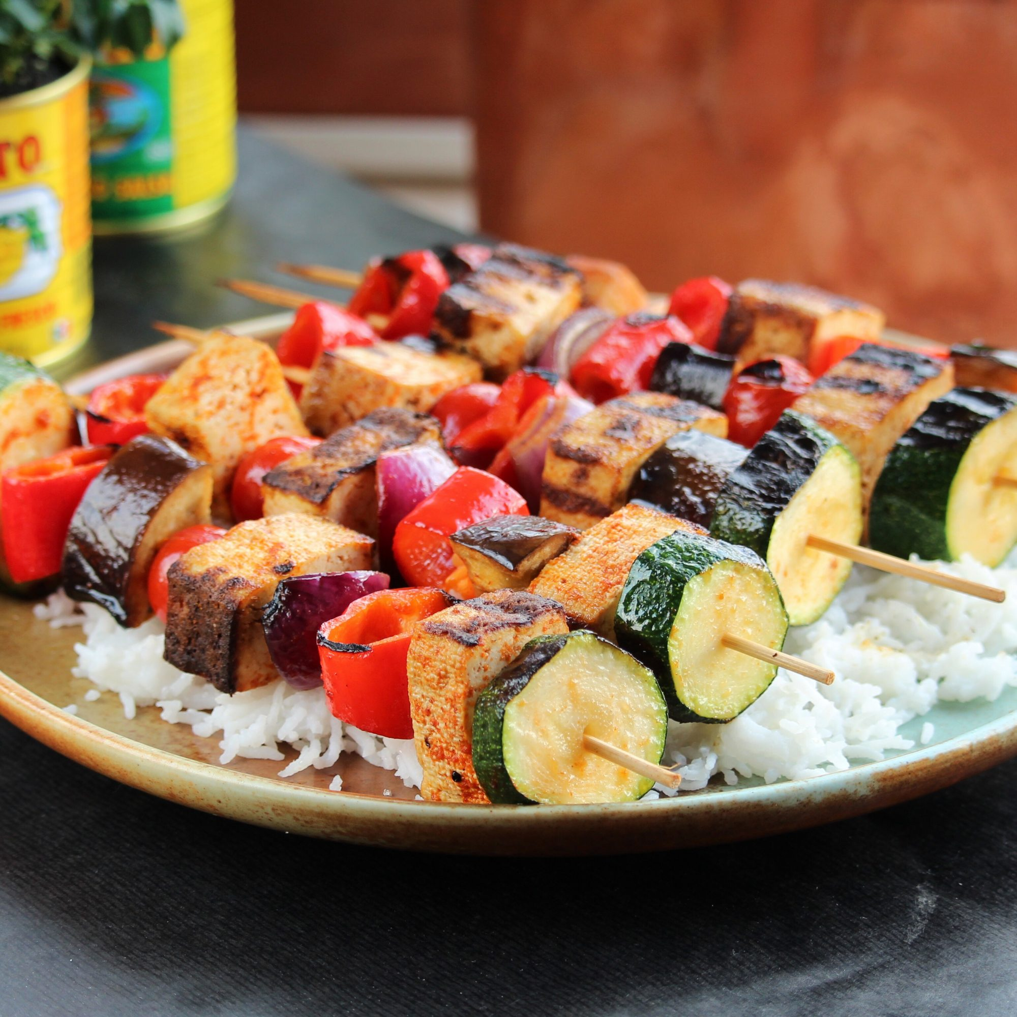 Grilled Tofu Skewers with Sriracha Sauce on a beige plate