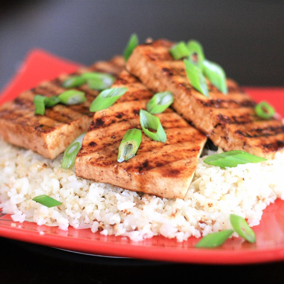Grilled Teriyaki Tofu with Roasted Cauliflower Rice on a red plate