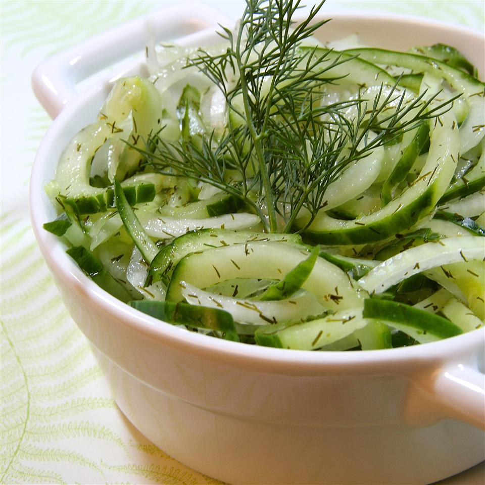 cucumber salad in white bowl with dill garnish