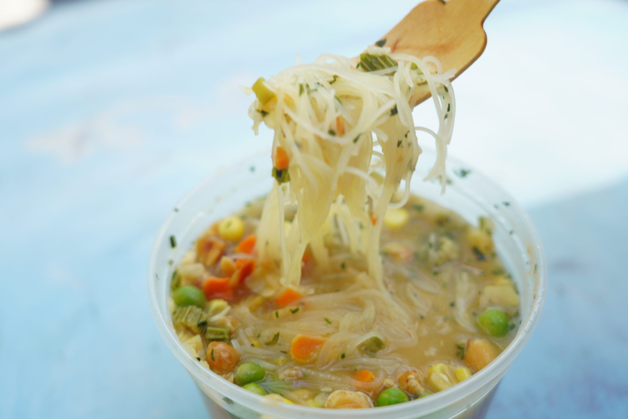 cup of backpackers' instant noodles with chopped peanuts and mixed vegetables