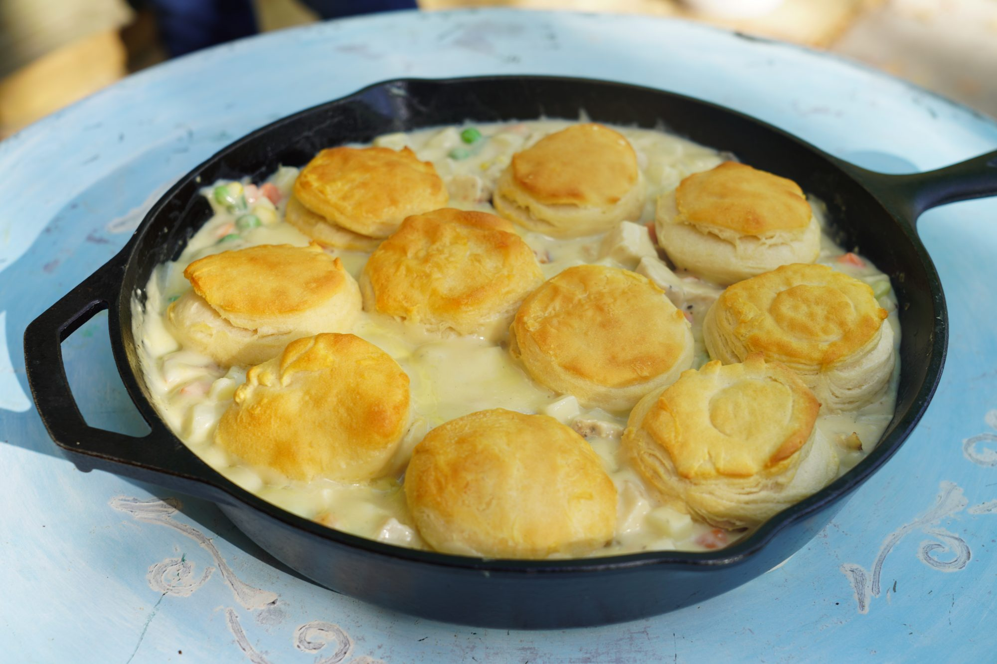 close up of campfire chicken pot pie cooked in a cast iron skillet and topped with biscuits