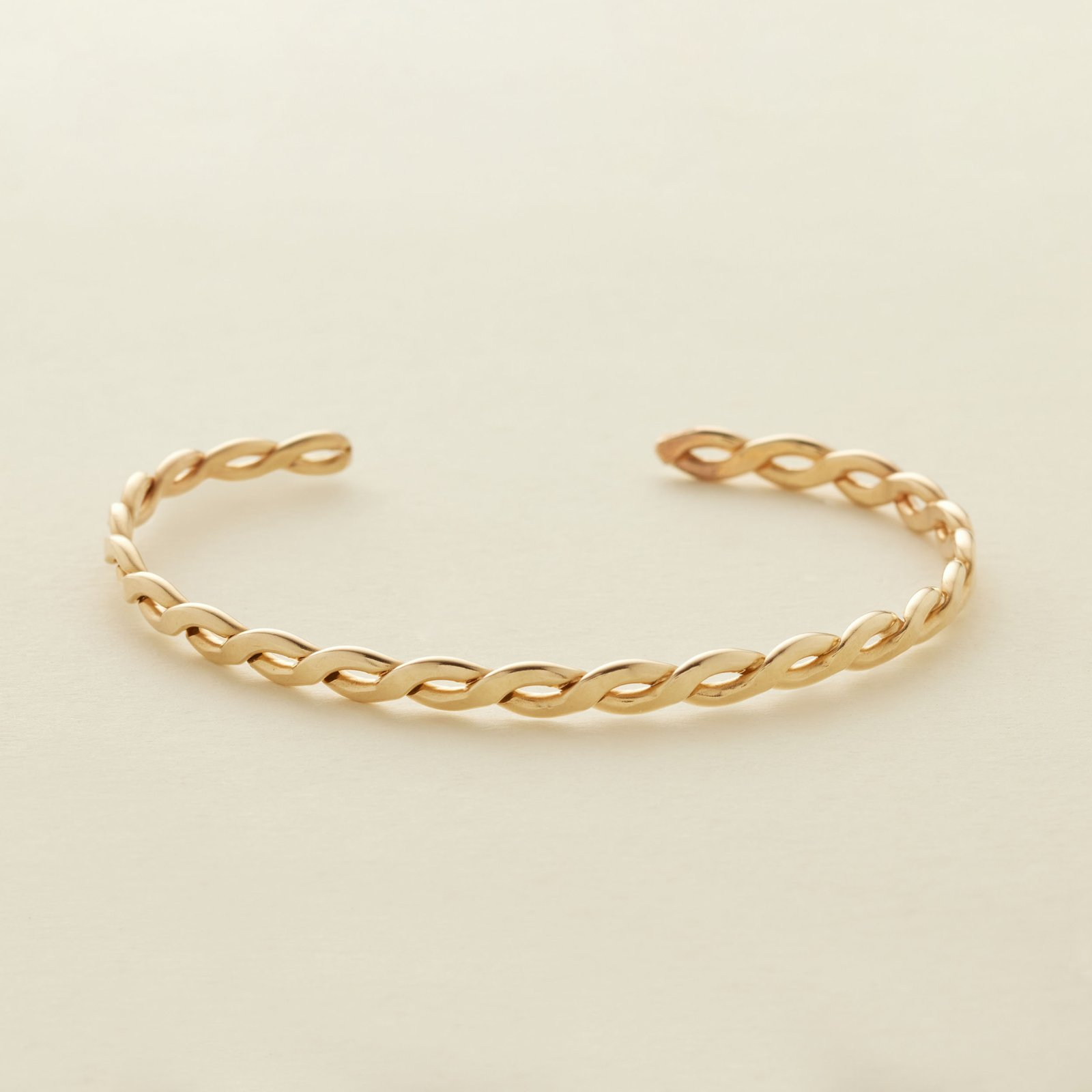 a gold braided bracelet on a cream background