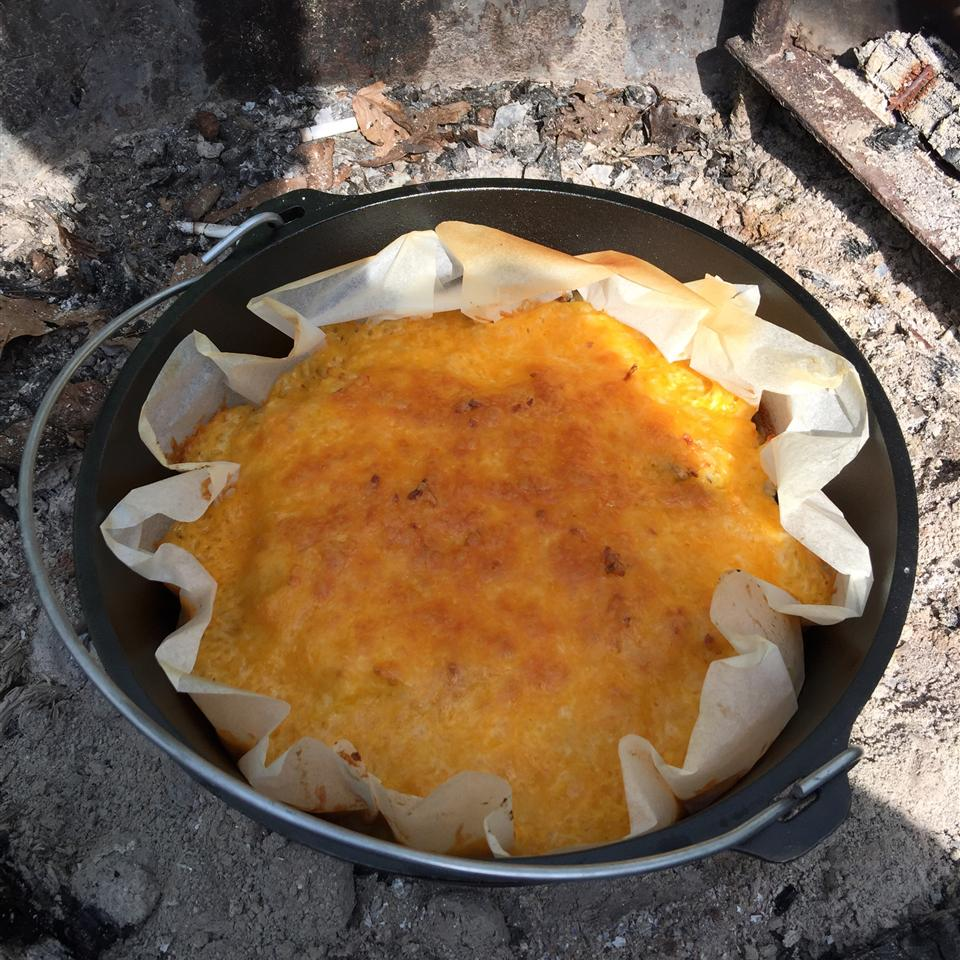 top-down view of a parchment lined cast iron Dutch oven holding a cheese-topped breakfast casserole in a bed of coals
