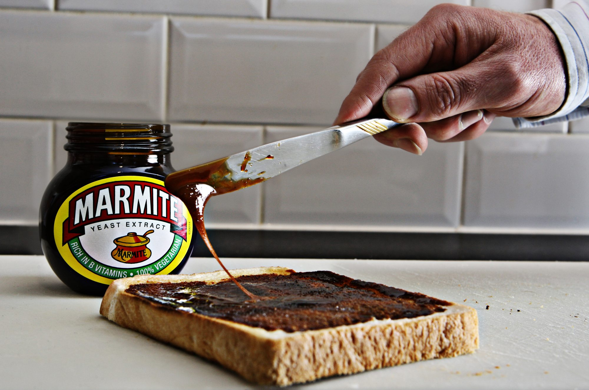 a jar of marmite next to a piece of toast being spread with marmite