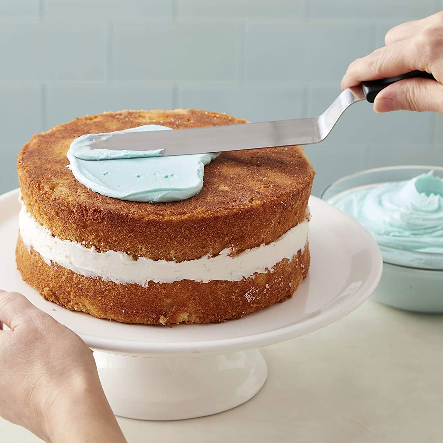 person frosting cake on cake stand using wilton angled spatula