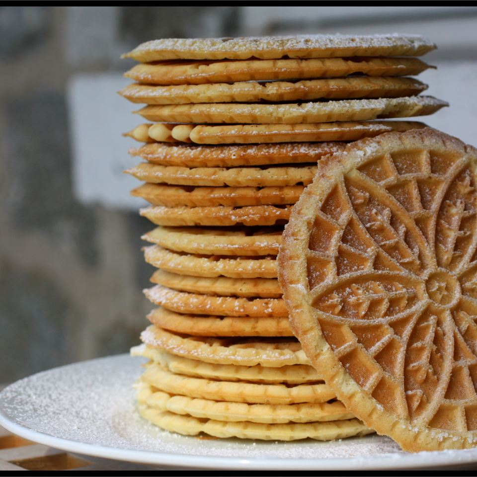 Pizzelles stacked on a white plate