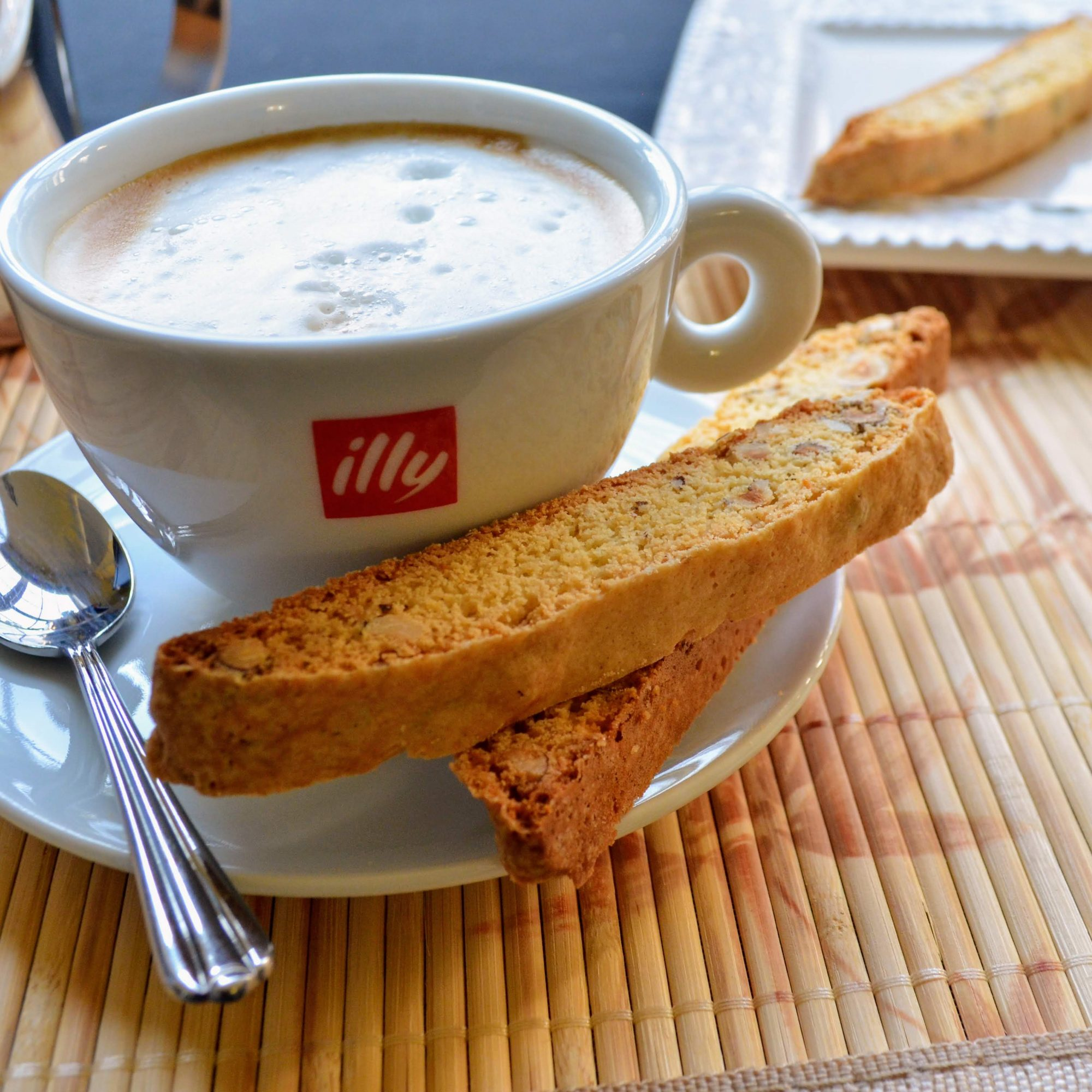 Chef John's Almond Biscotti with coffee on a white plate