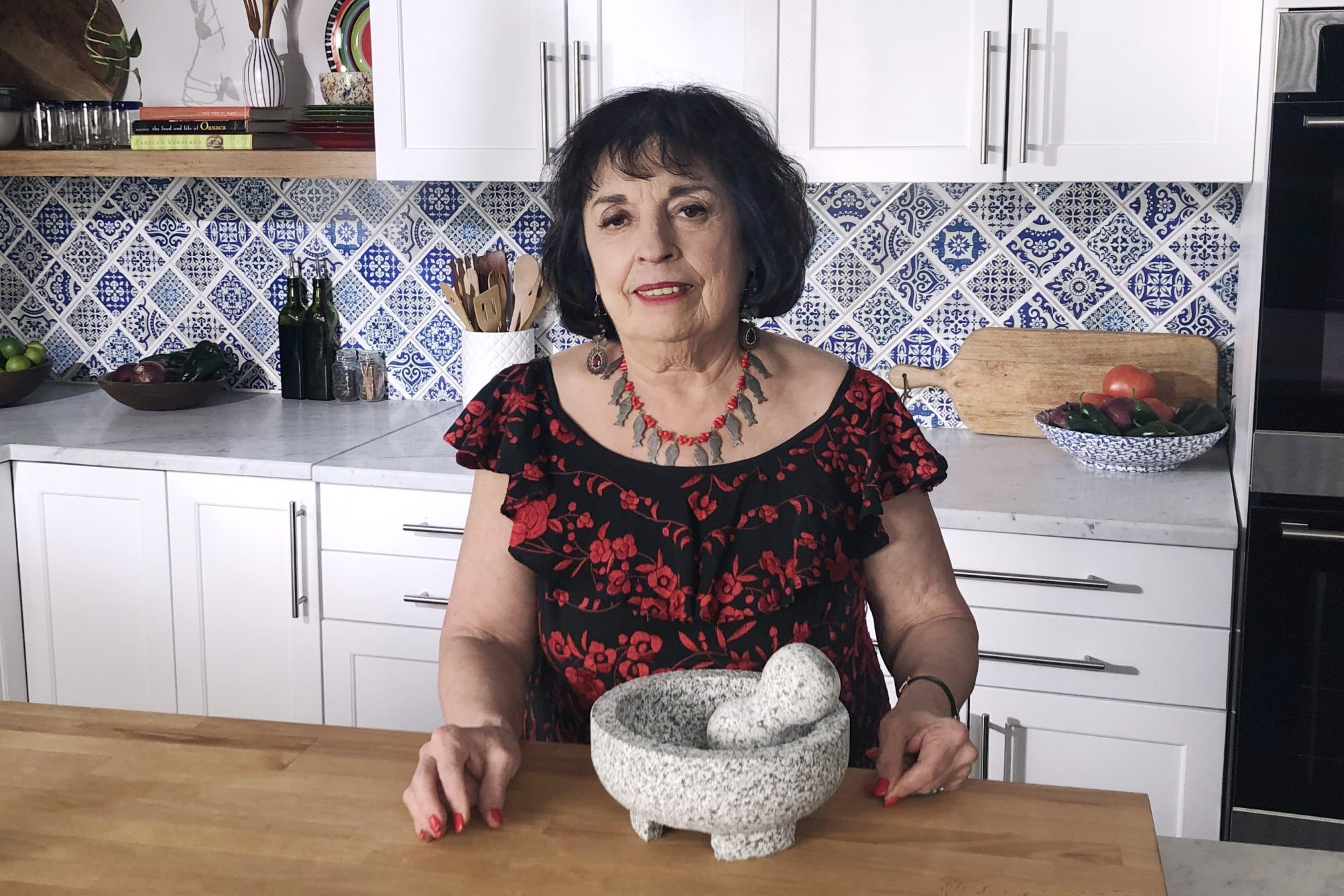 Zarela Martinez in the kitchen with mortar and pestle on the island