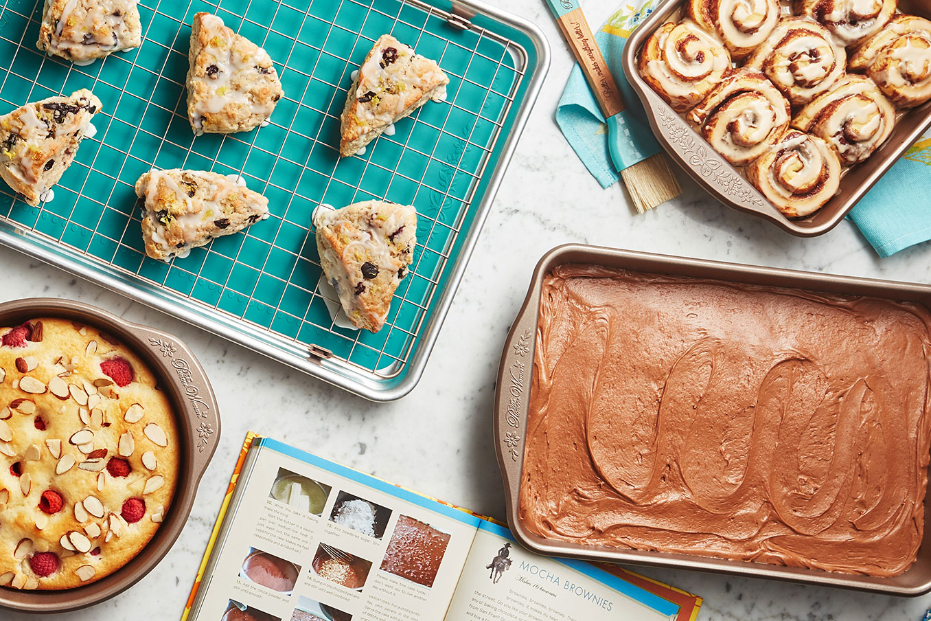 pioneer woman bakeware items with scones, cinnamon rolls, chocolate cake, and crumble