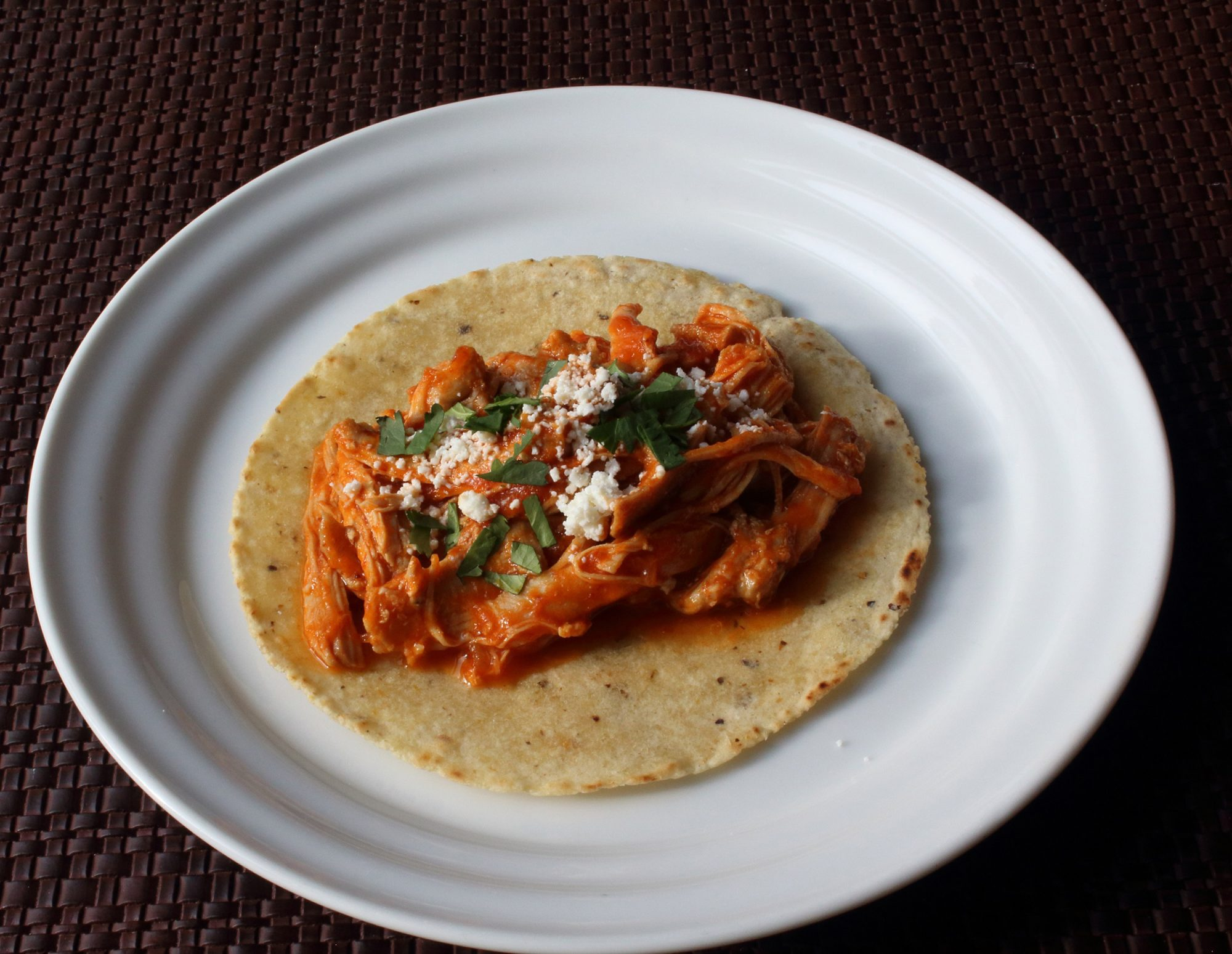shredded chicken with tomato sauce on tortilla