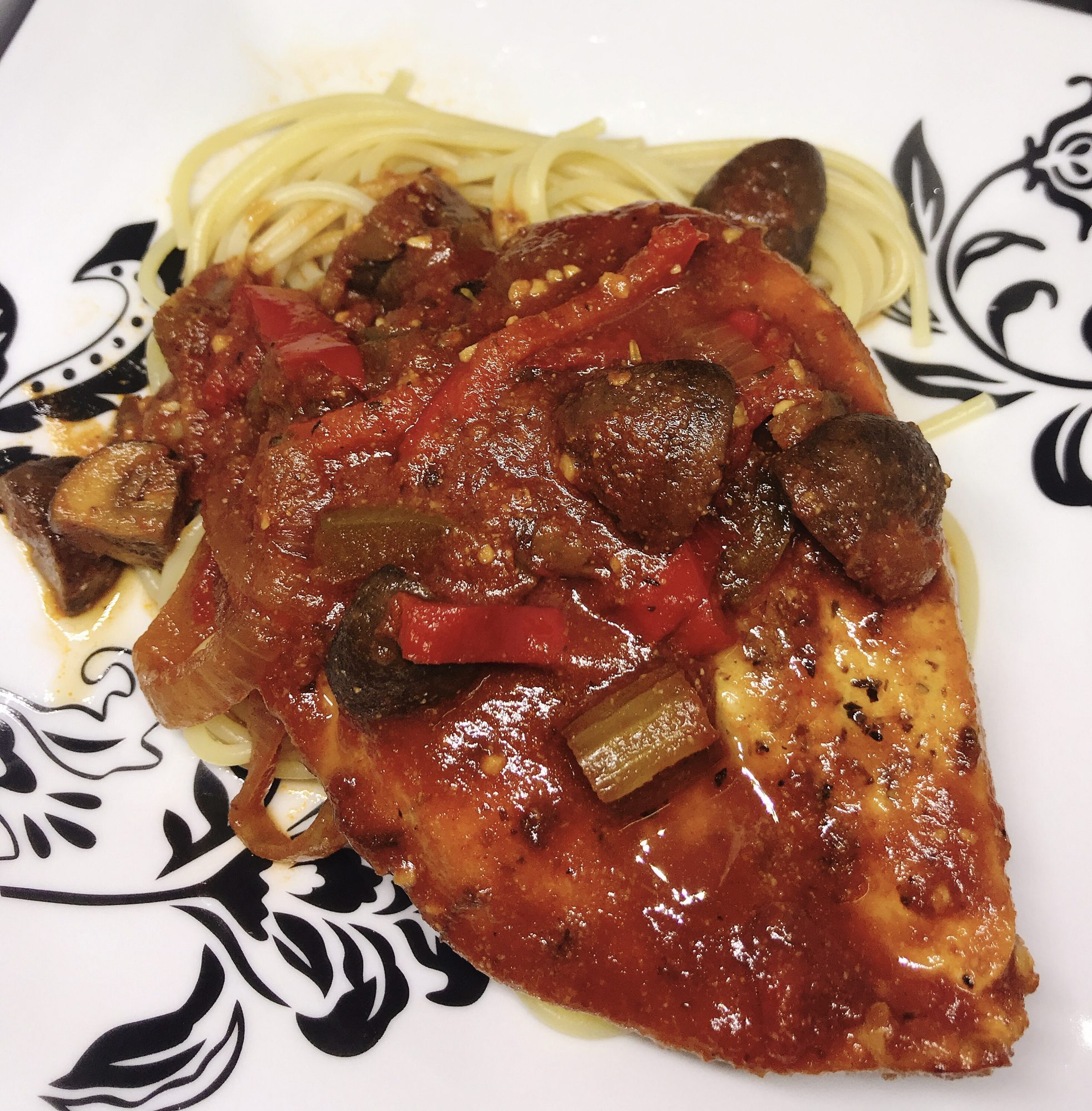 chicken thigh with red sauce over spaghetti