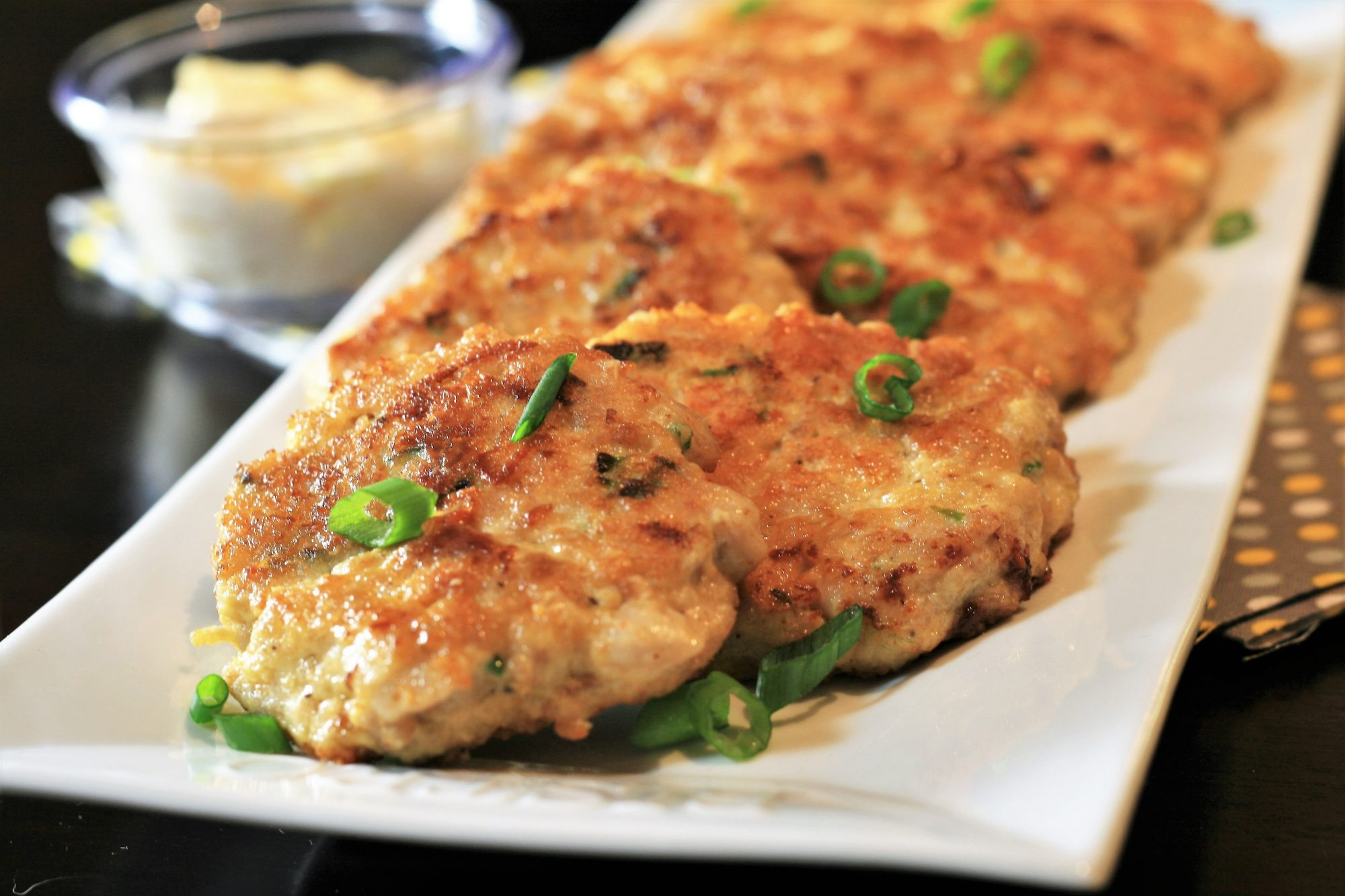 chicken fritters on white platter with green onions