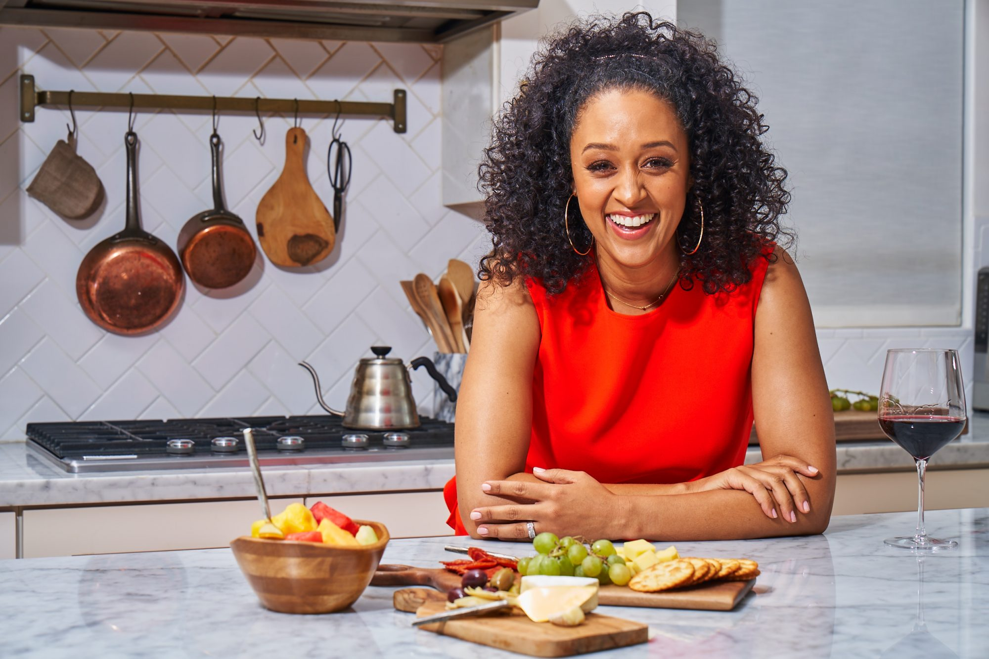 Tia Mowry in the kitchen beside charcuterie board on the island