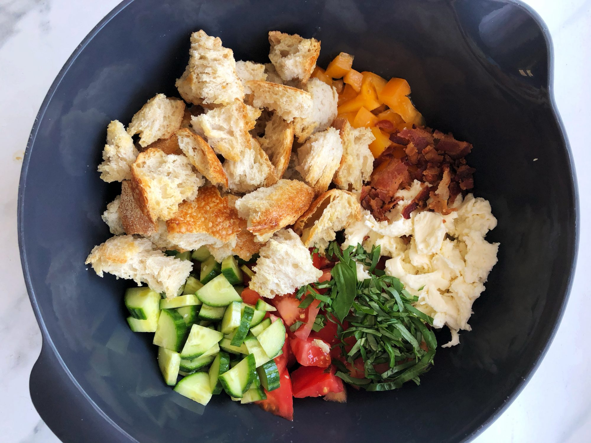panzanella ingredients in a mixing bowl