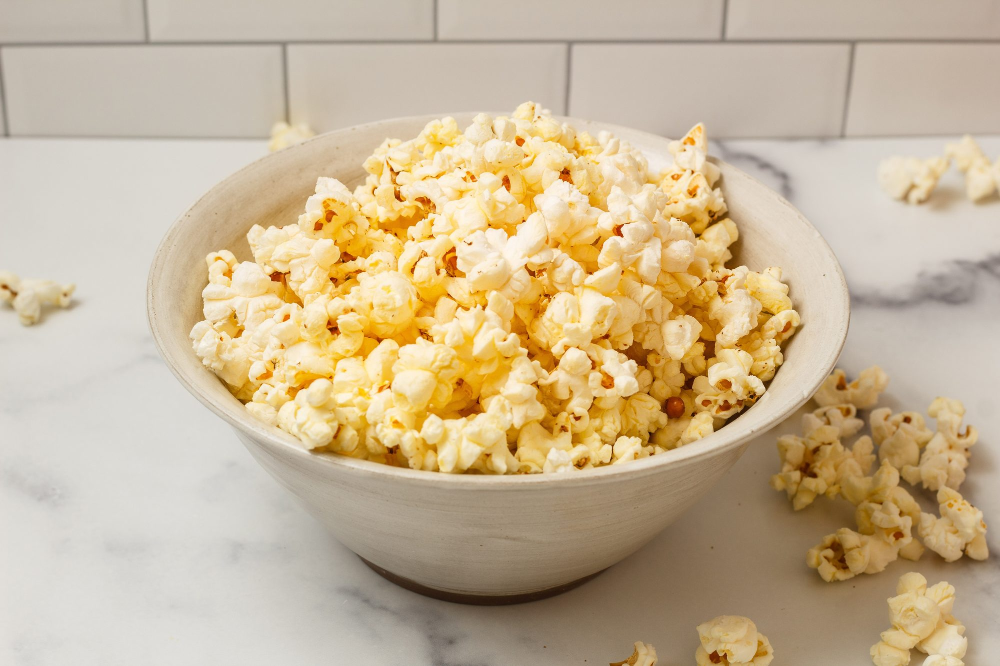 freshly popped popcorn sits in a white stoneware bowl on a white counter with white subway tiles behind it