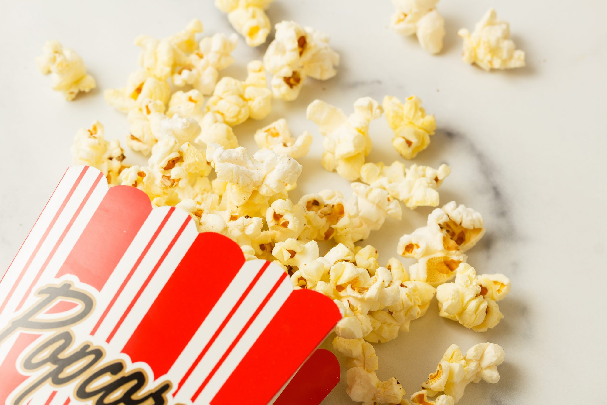 popcorn in a red striped box spilling out onto a marble counter