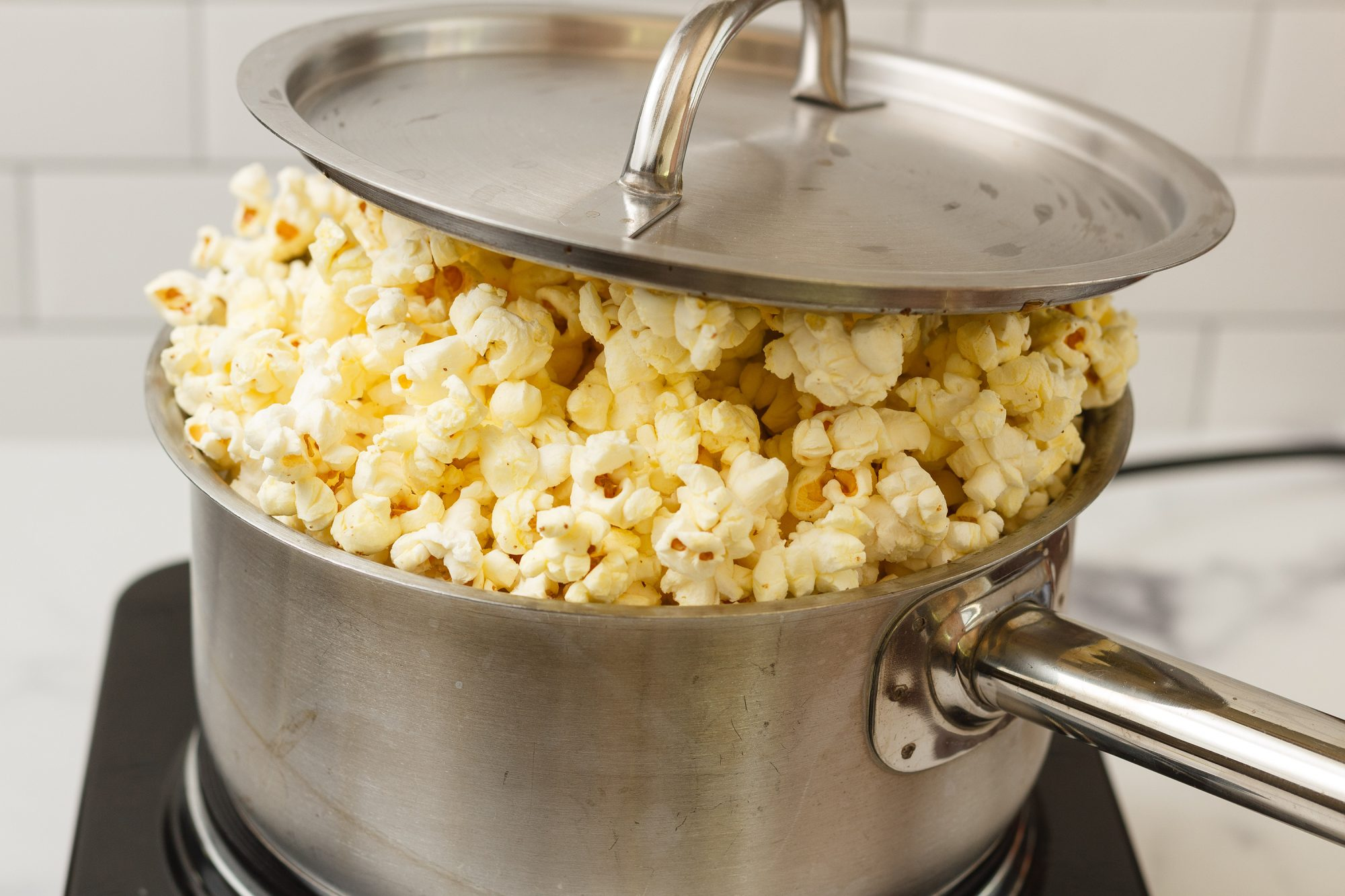 popcorn popping in a saucepan with a lid on top