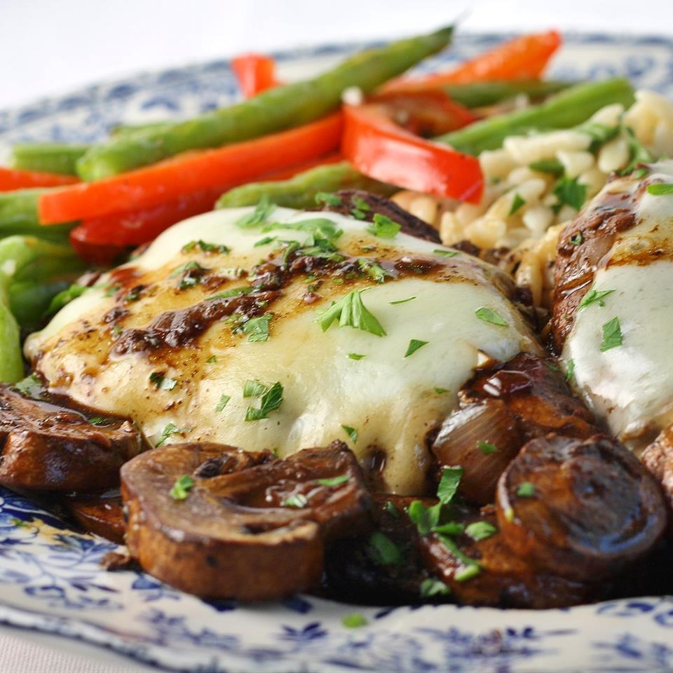 chicken in sauce with mushrooms and cheese on top