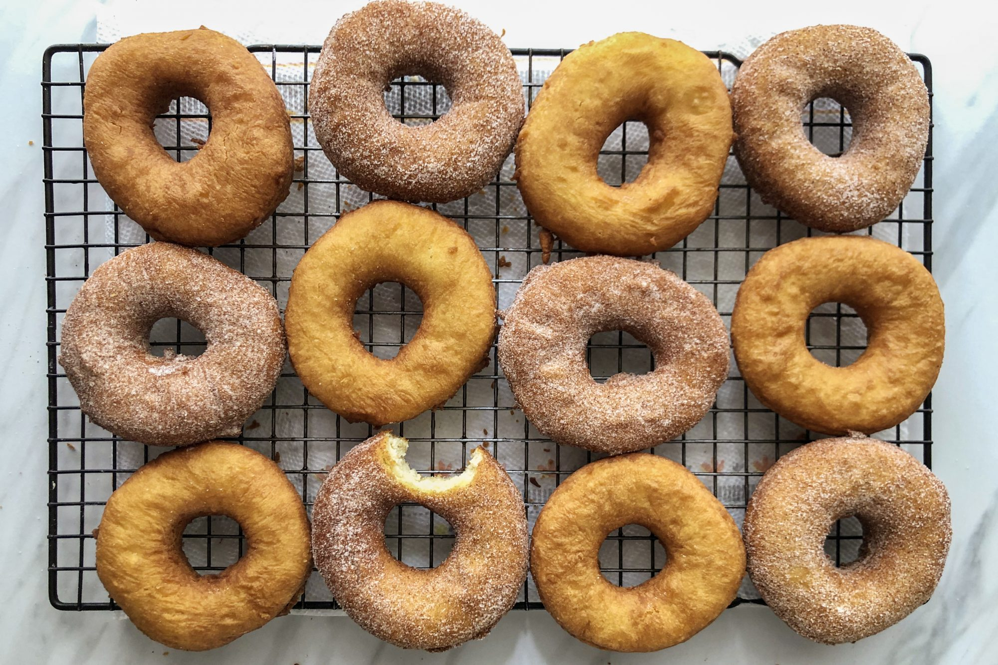 A dozen freshly fried grandma's old-fashioned cake donuts sit on a cooling rack. half are dusted in cinnamon and sugar, and one has a bite taken out