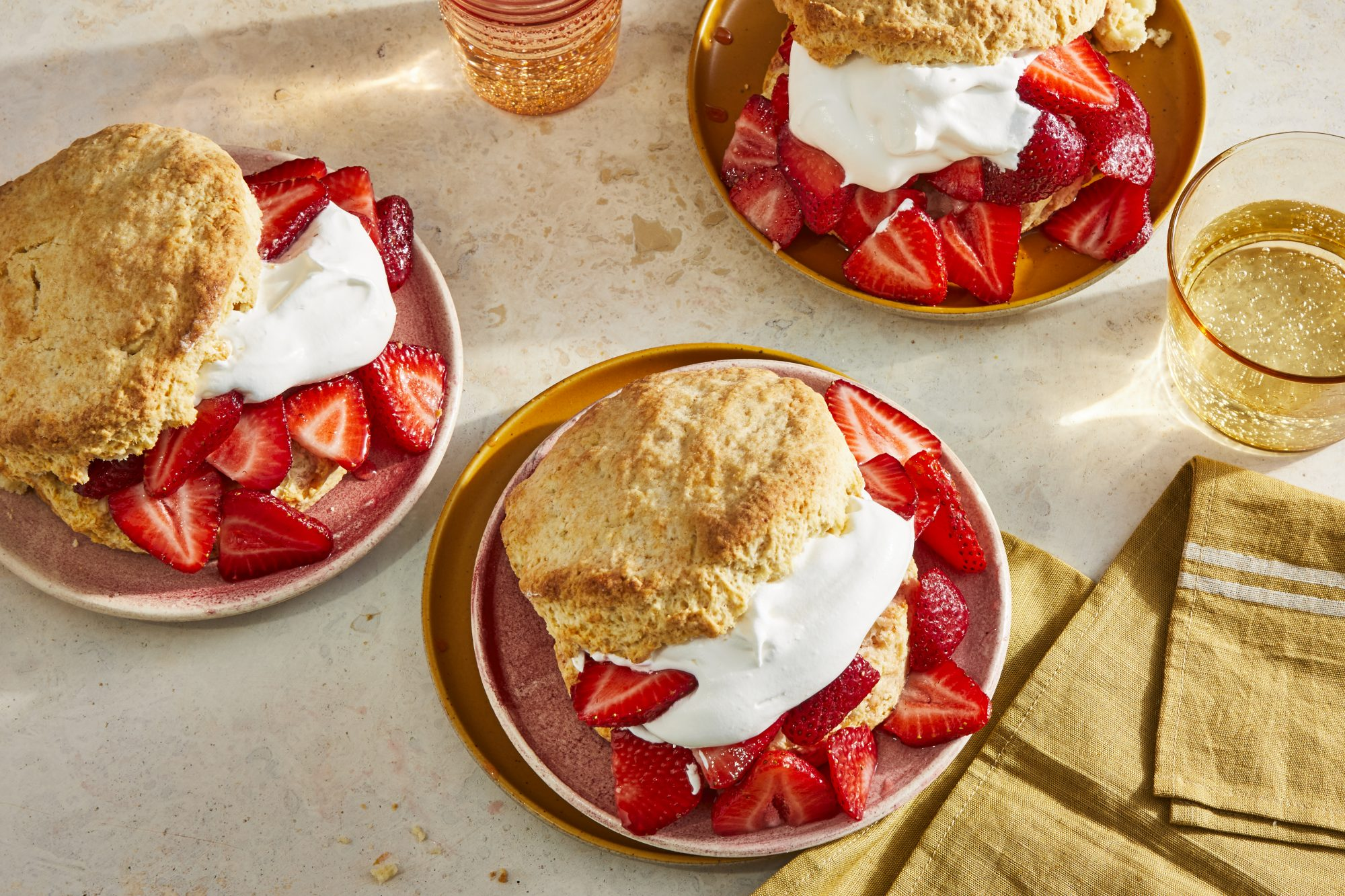 3 plates of beautiful strawberry shortcakes with scratch made biscuits, fluffy whipped cream and fresh strawberries