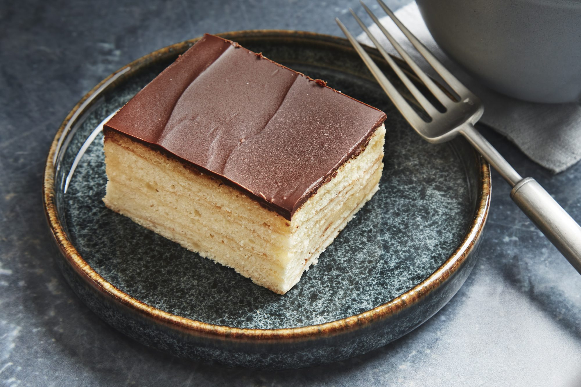 a single slice of a delicate layer cake known as baumkuchen topped with a layer of chocolate sitting on a small dessert plate with a fork