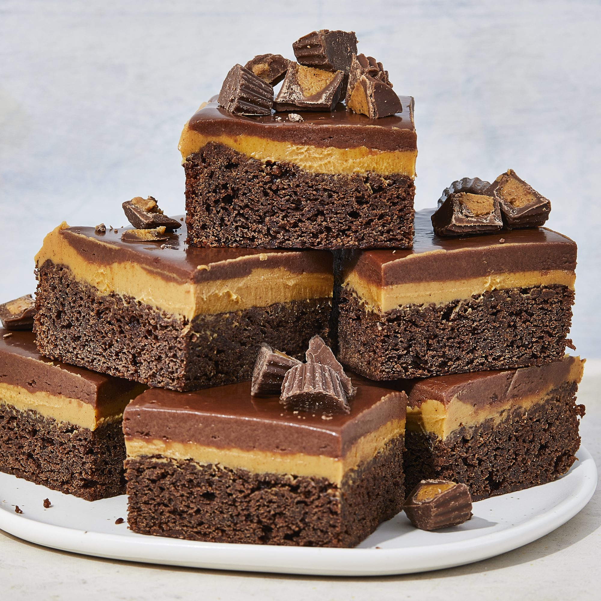 Peanut butter fudge cake slices stacked on a plate and sprinkled with chopped peanut butter cups