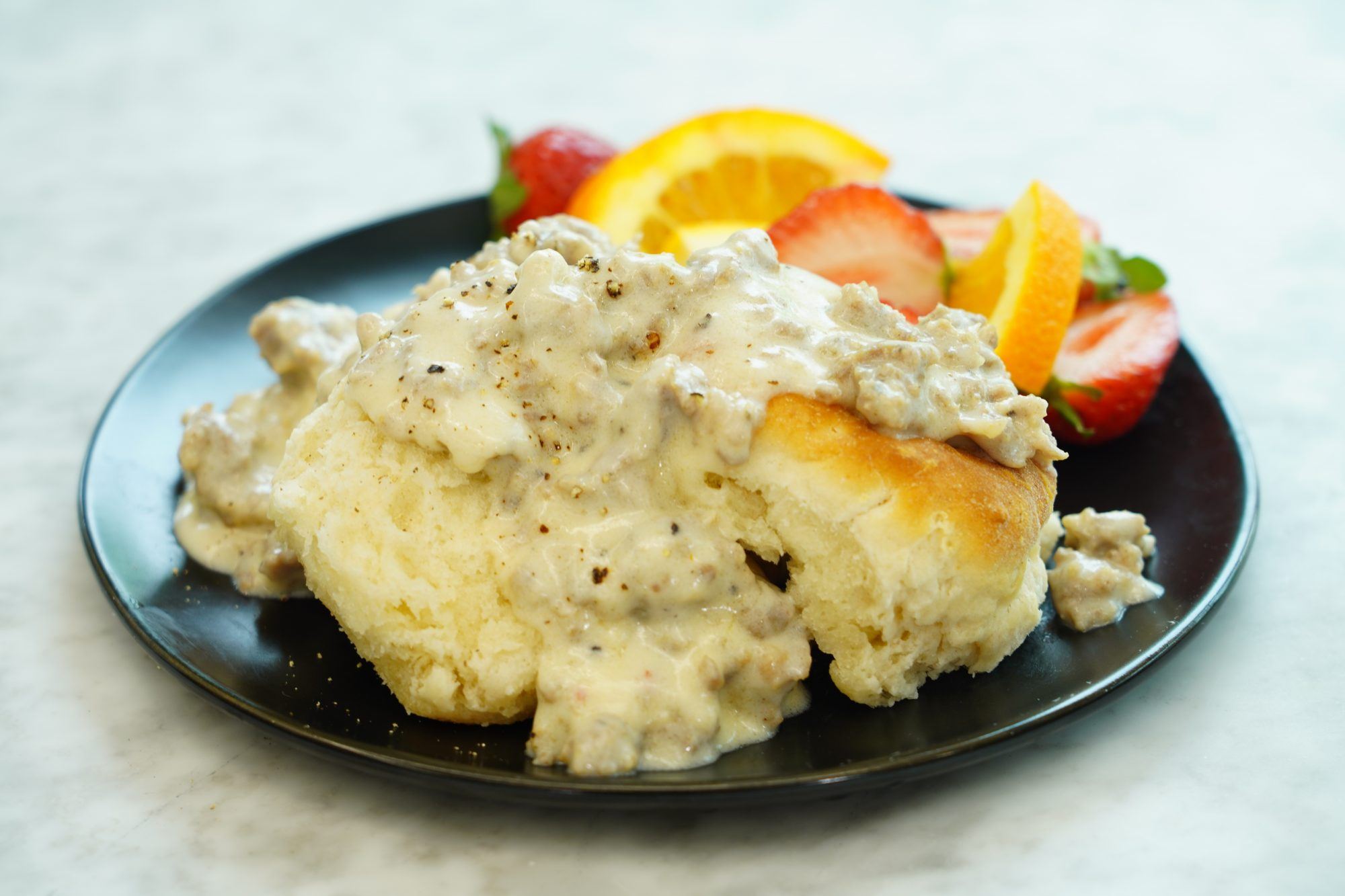 plate of creamy sausage gravy served over open-face biscuits with fruit on the side