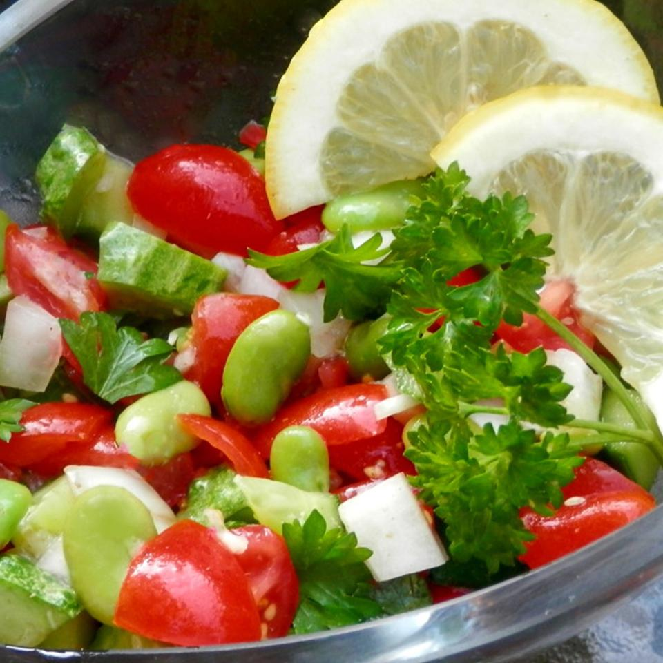 bowl of salad with fresh fava beans, tomatoes, cucumber, and parsley