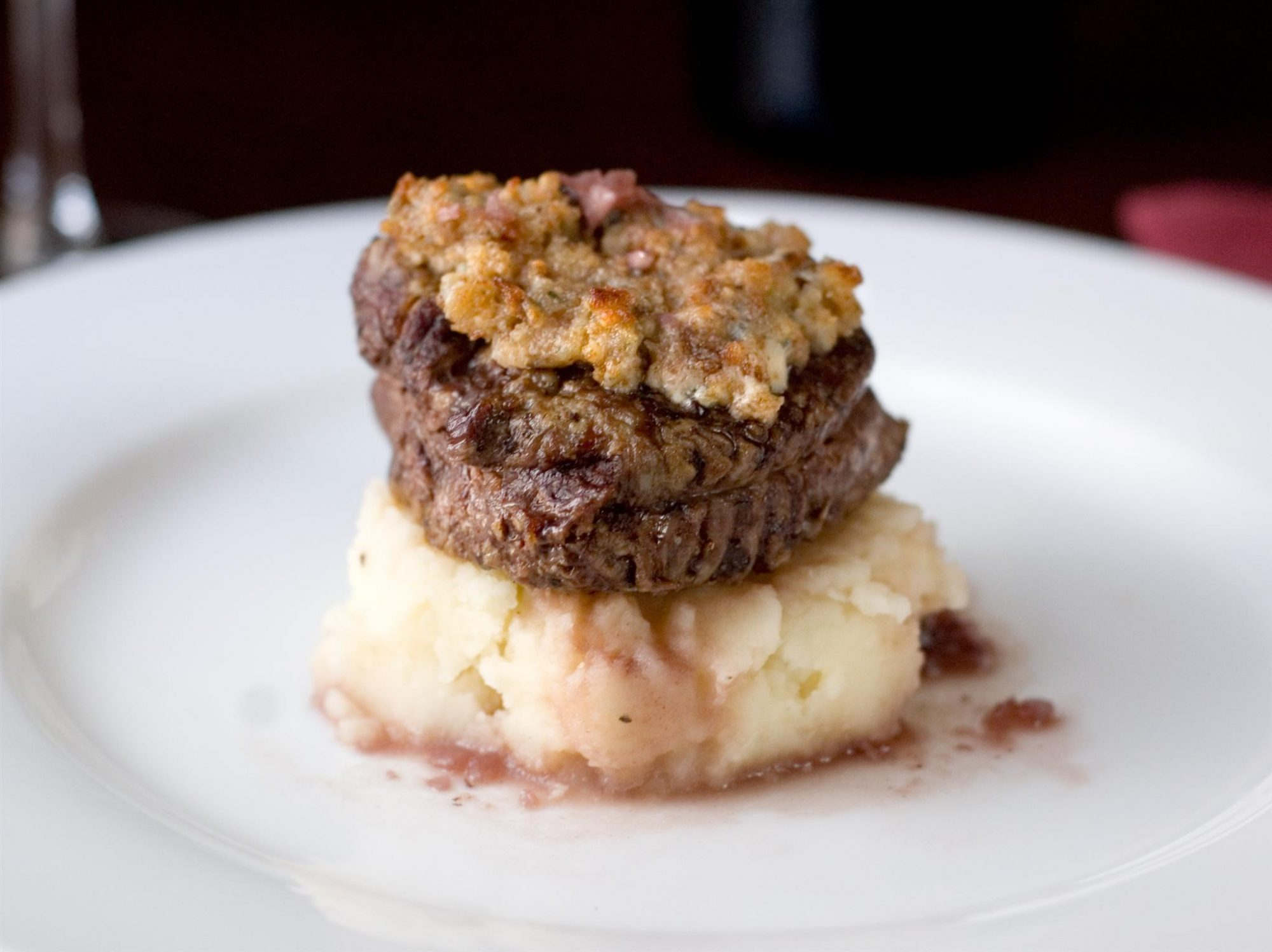a filet topped with blue cheese served on a bed of mashed potatoes and sauce served centered on a white plate. Looks fancy!