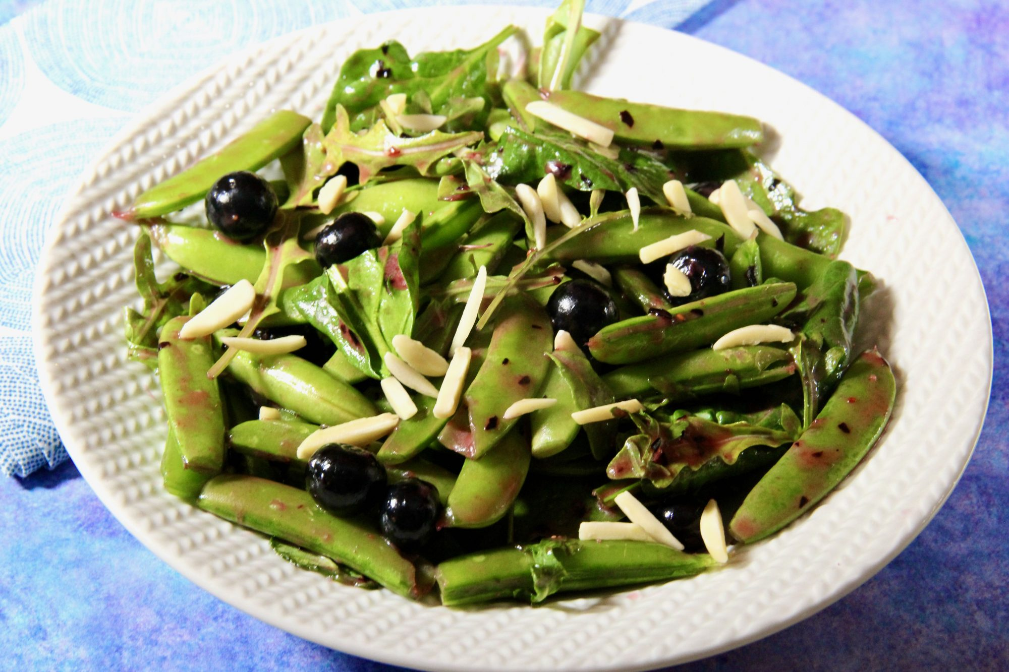 bowl of sugar snap peas, blueberries, and slivered almonds