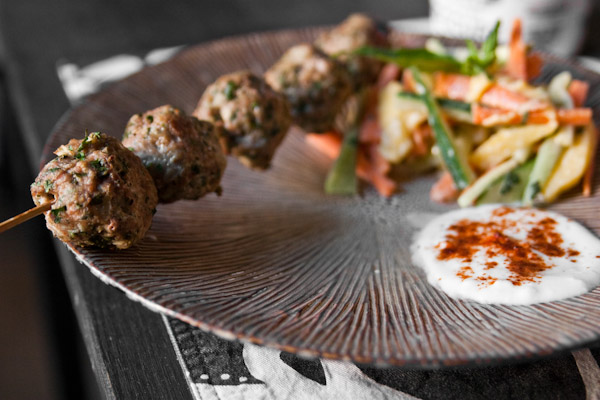 closeup of a skewer of ground beef kebabs on a plate with yogurt sauce and salad in the background
