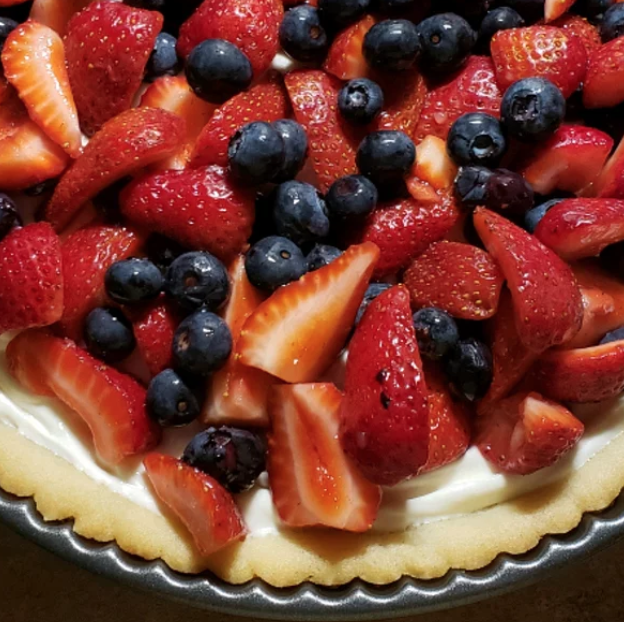 You only need three ingredients to make this vibrant dessert pizza: a package of refrigerated sugar cookie dough, a jar of marshmallow creme, and your favorite fresh fruits.