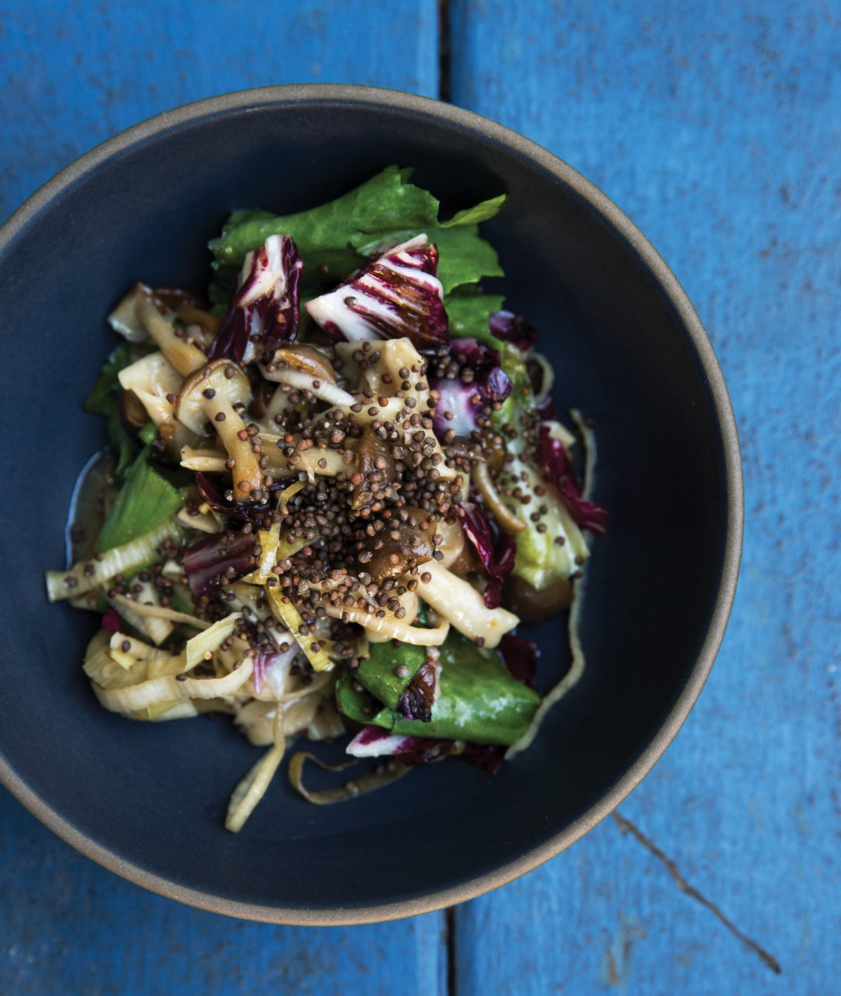 mushroom noodles in bowl with greens and wild sesame seeds
